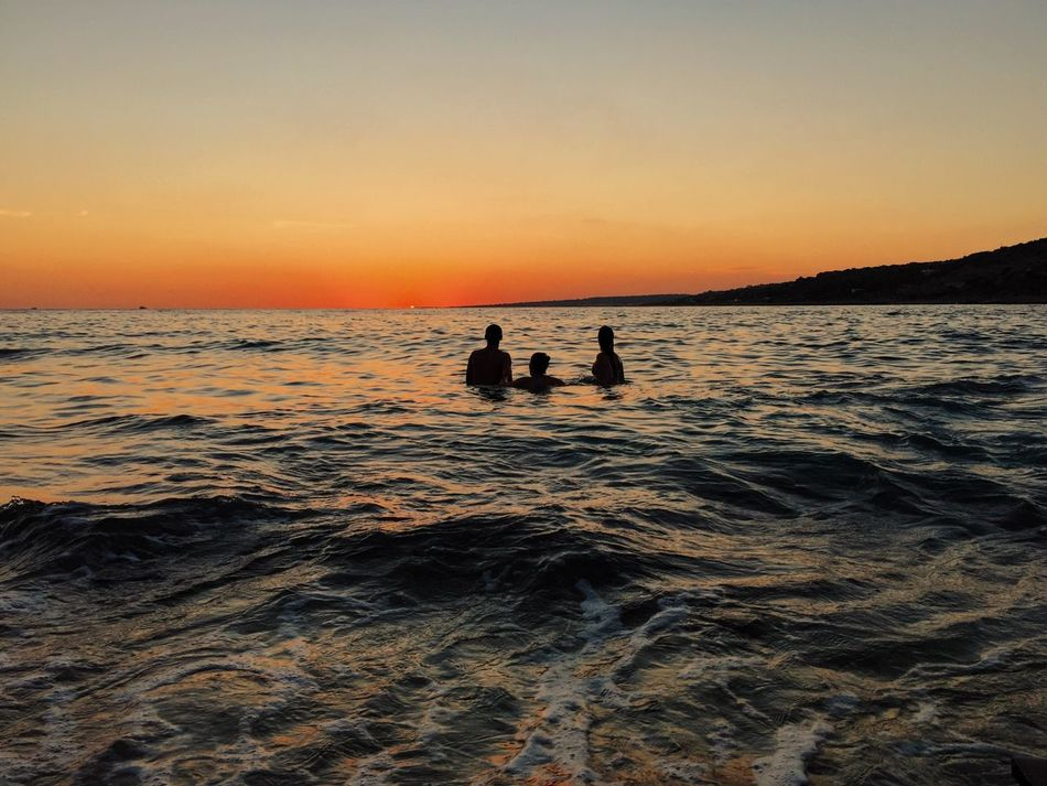 Live For The Story Sunset Silhouette Beauty In Nature Sea Scenics Orange Color Nature Water Sky Beach Leisure Activity Real People Wave Tranquility Outdoors Clear Sky Togetherness Horizon Over Water Friendship Day Summer BYOPaper!