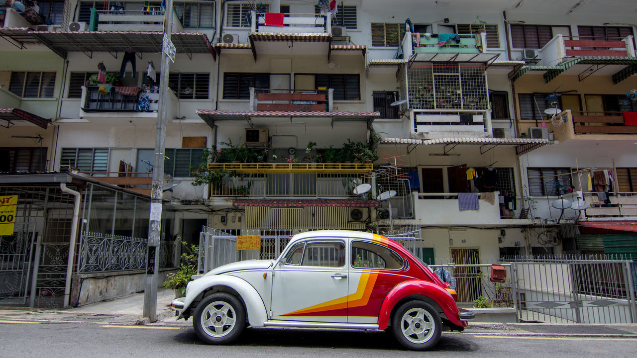 Side on view of a well maintained VW beetle parked in a residential street of apartments in Kuala Lumpur. Alloy Wheels Apartment Beetle Bug Car City Classic Classic Car Day Detail Maintained Modern No People Outdoors Racing Stripes Rims Side Street Slope Stripes Pattern Volkswagen VW VW Beetle White Wheel