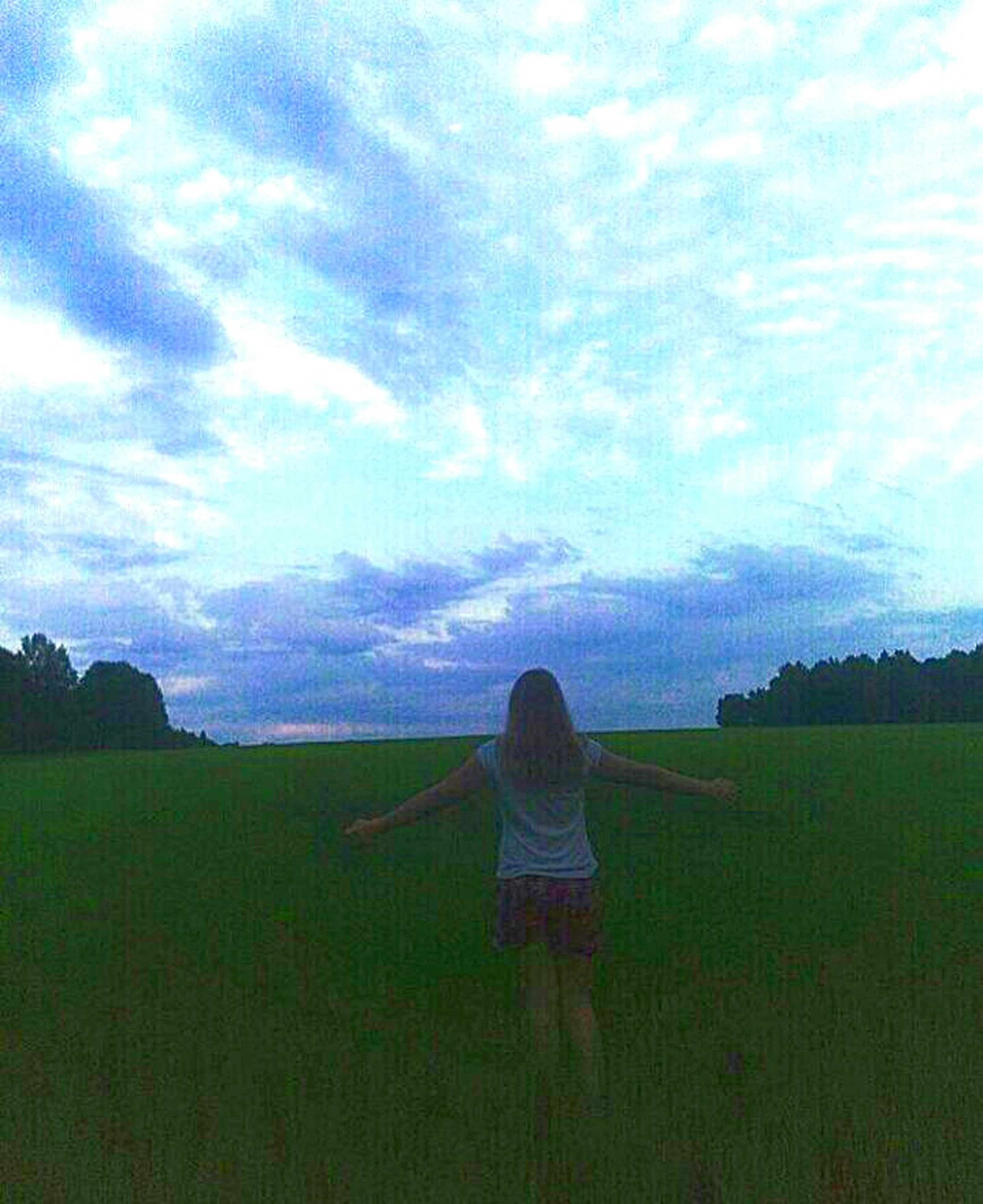 rear view, sky, real people, nature, one person, tranquility, cloud - sky, field, landscape, leisure activity, tranquil scene, green color, women, beauty in nature, outdoors, grass, day, people