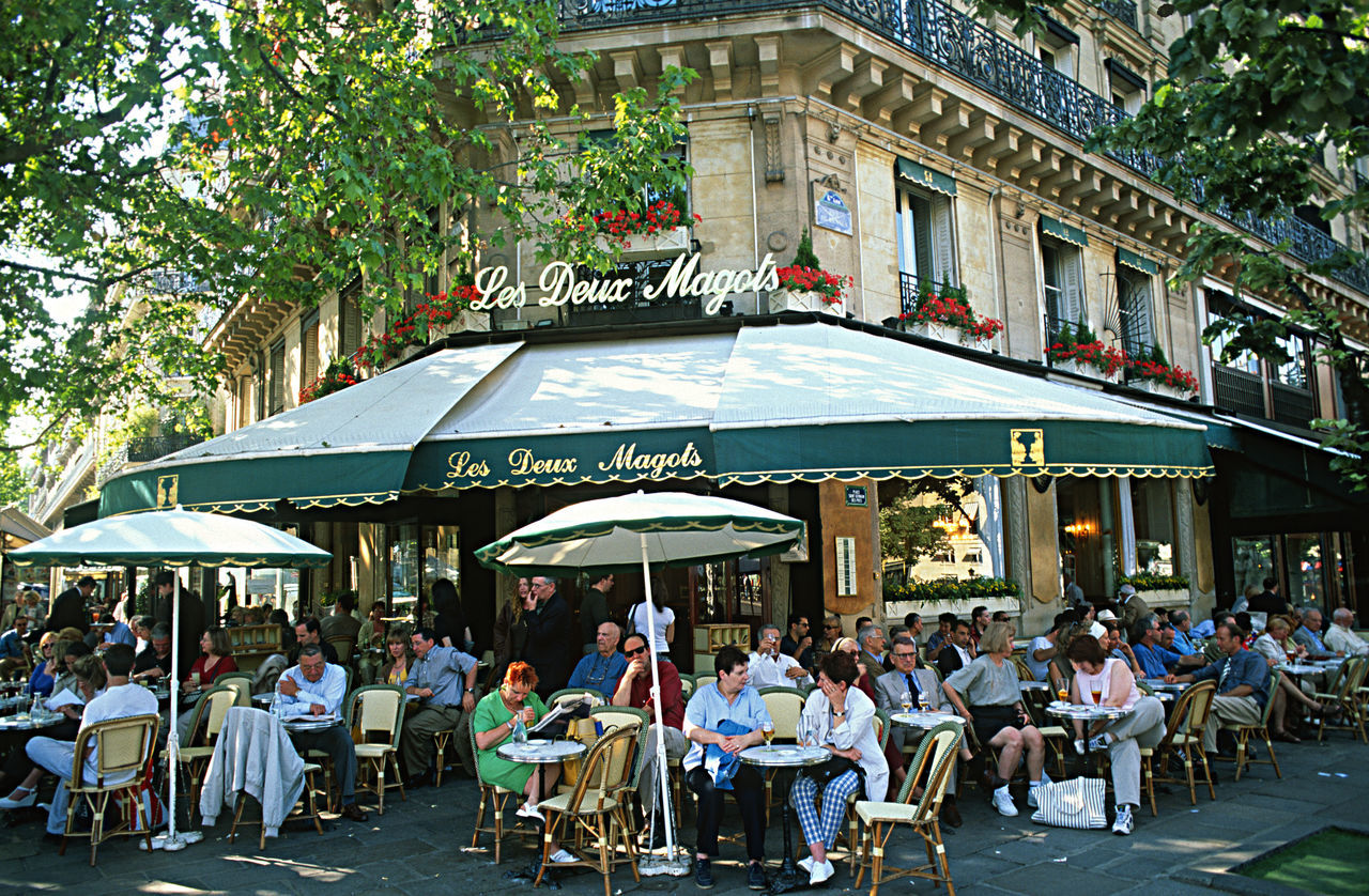 table, large group of people, sidewalk cafe, restaurant, chair, building exterior, food and drink, cafe, outdoors, day, architecture, built structure, men, city, people, women, awning, adult, adults only