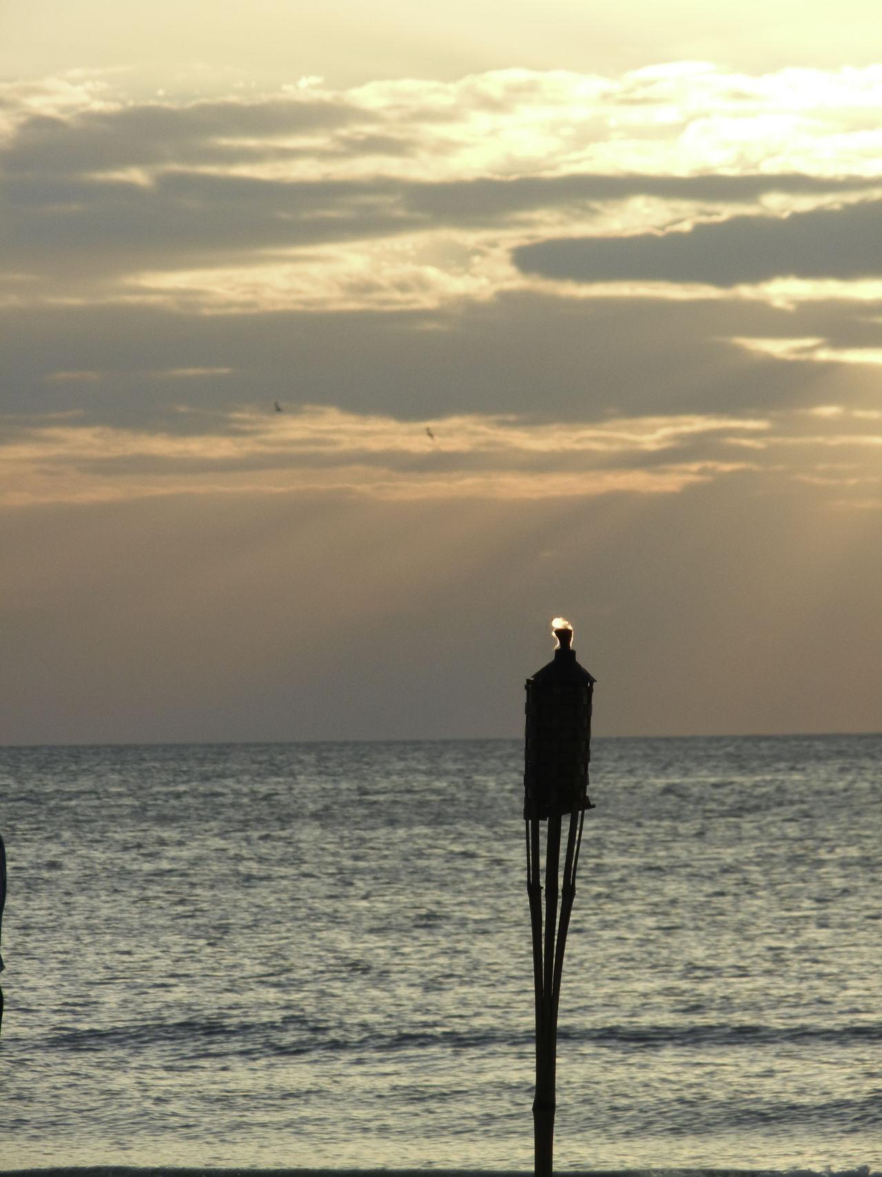 Flame of a tiki torch lantern captured against a coastal sunset. Beach Beachphotography Cloud Coastal Dramatic Sky Dusk Flame Getting Away From It All Horizon Over Water Lantern Light Moody Sky Ocean Outdoors Scenics Sea Seascape Sky Sun Sunrays Sunset Sunset Silhouettes Tiki Torch Torch Tropical