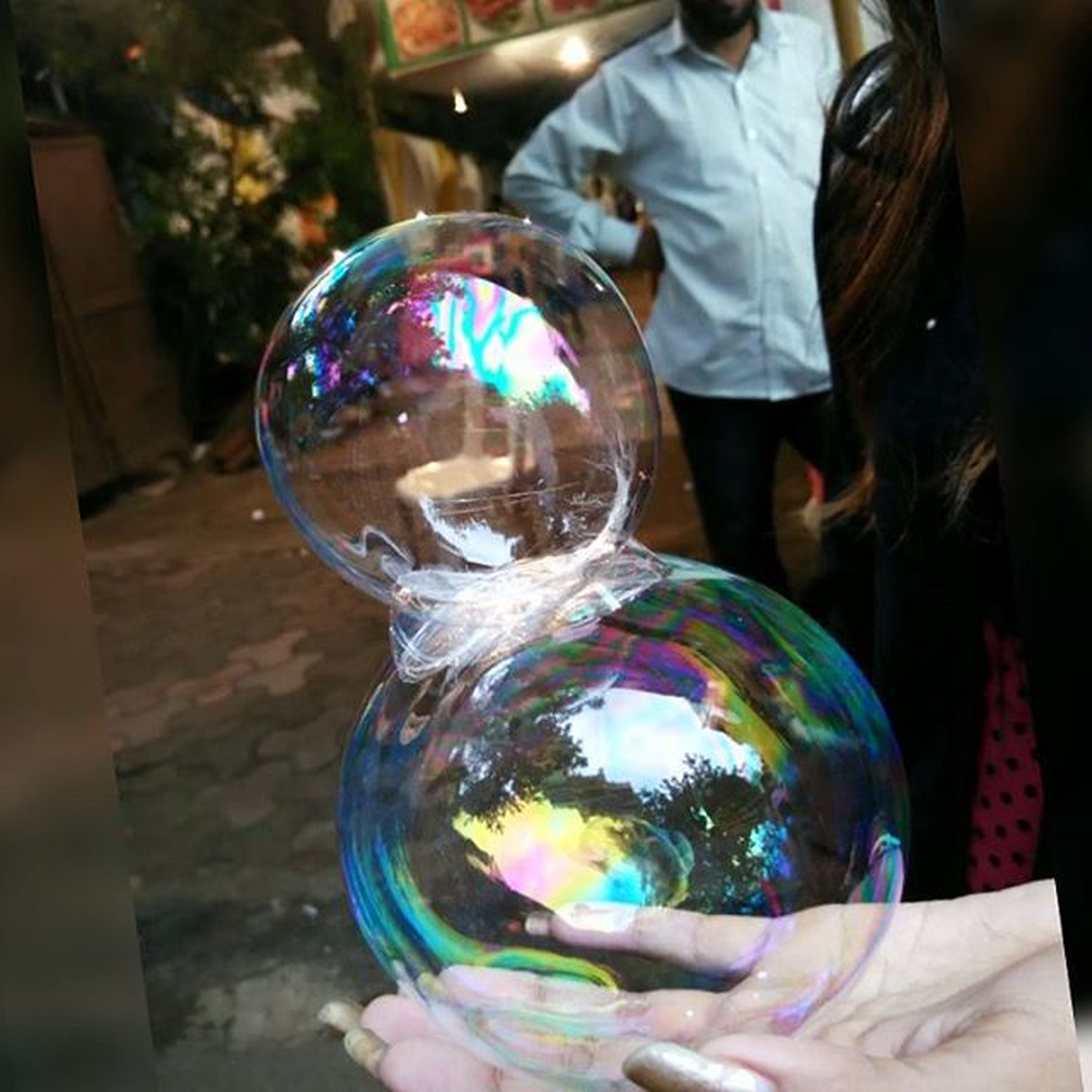 lifestyles, leisure activity, focus on foreground, bubble, unrecognizable person, multi colored, person, holding, men, motion, sphere, rear view, close-up, standing, part of, incidental people