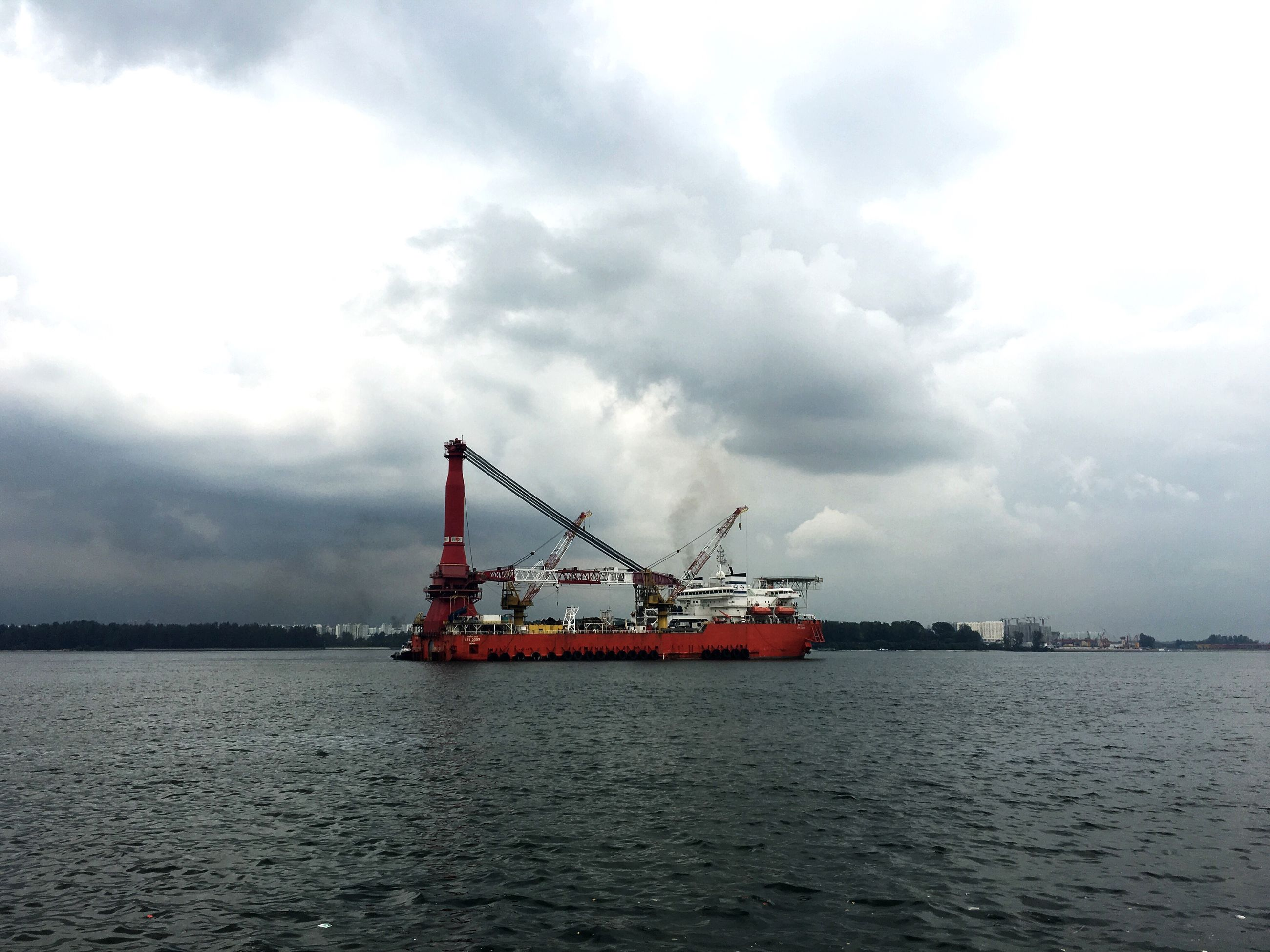 water, waterfront, transportation, sky, sea, nautical vessel, cloud - sky, mode of transport, crane - construction machinery, cloudy, cloud, sailing, cloudscape, nature, tranquil scene, day, industry, scenics, outdoors, shipping, journey, tranquility, no people, development, beauty in nature, commercial dock, moody sky, ocean