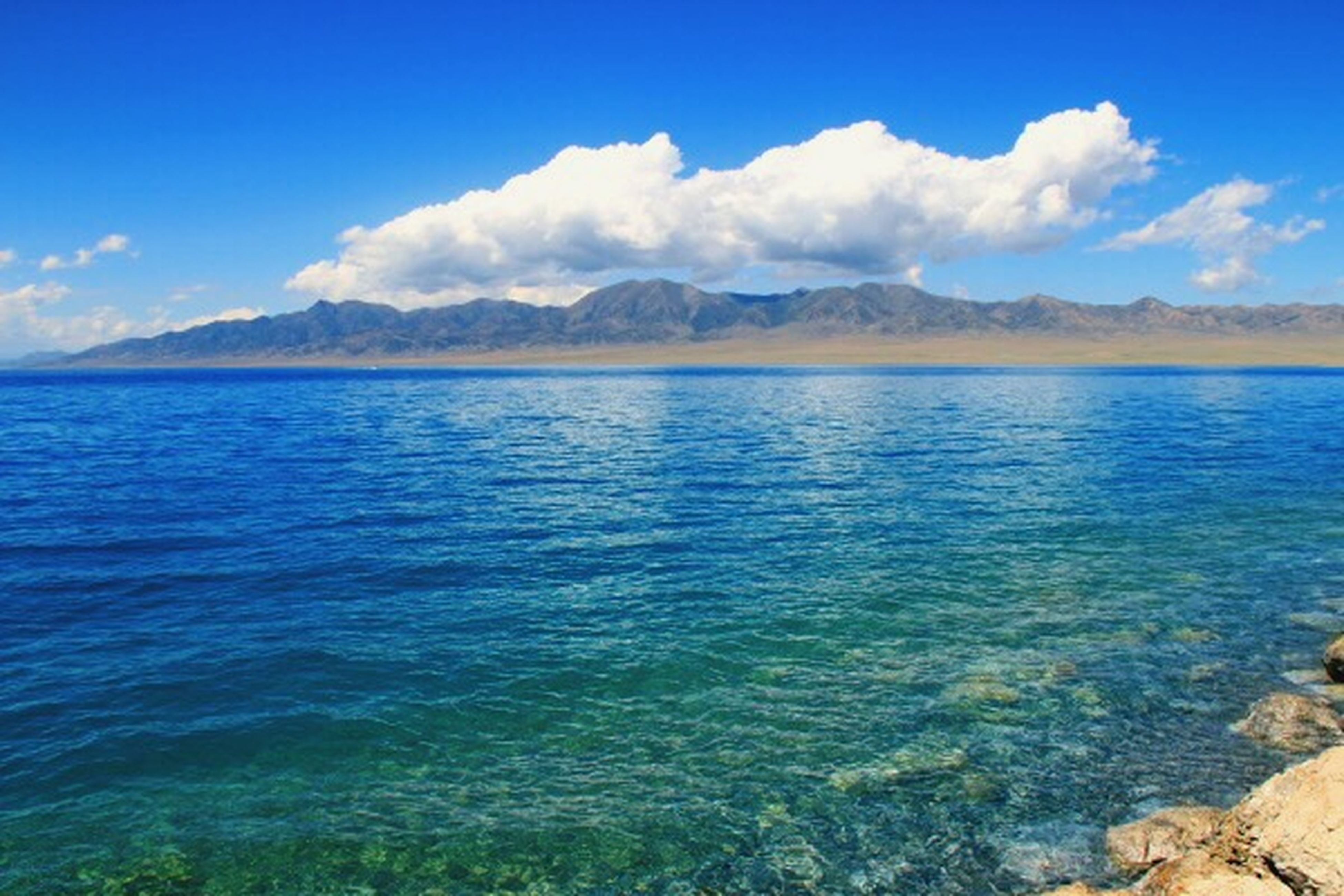 mountain, water, sky, tranquil scene, scenics, tranquility, mountain range, beauty in nature, blue, sea, cloud - sky, nature, cloud, lake, idyllic, rippled, waterfront, non-urban scene, day, calm