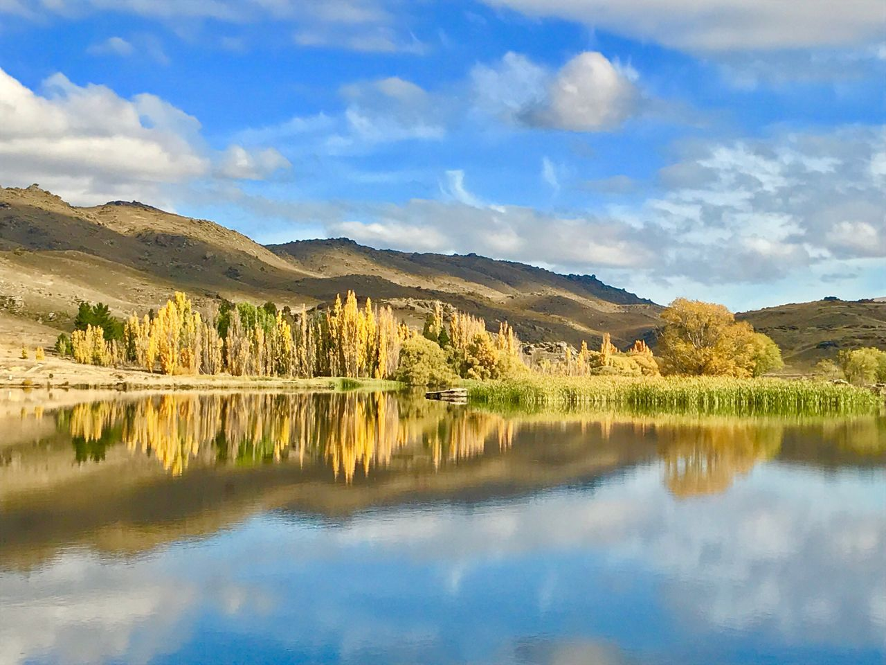 reflection, tranquil scene, scenics, tranquility, beauty in nature, water, waterfront, nature, mountain, day, sky, no people, outdoors, lake, cloud - sky, landscape, mountain range, tree