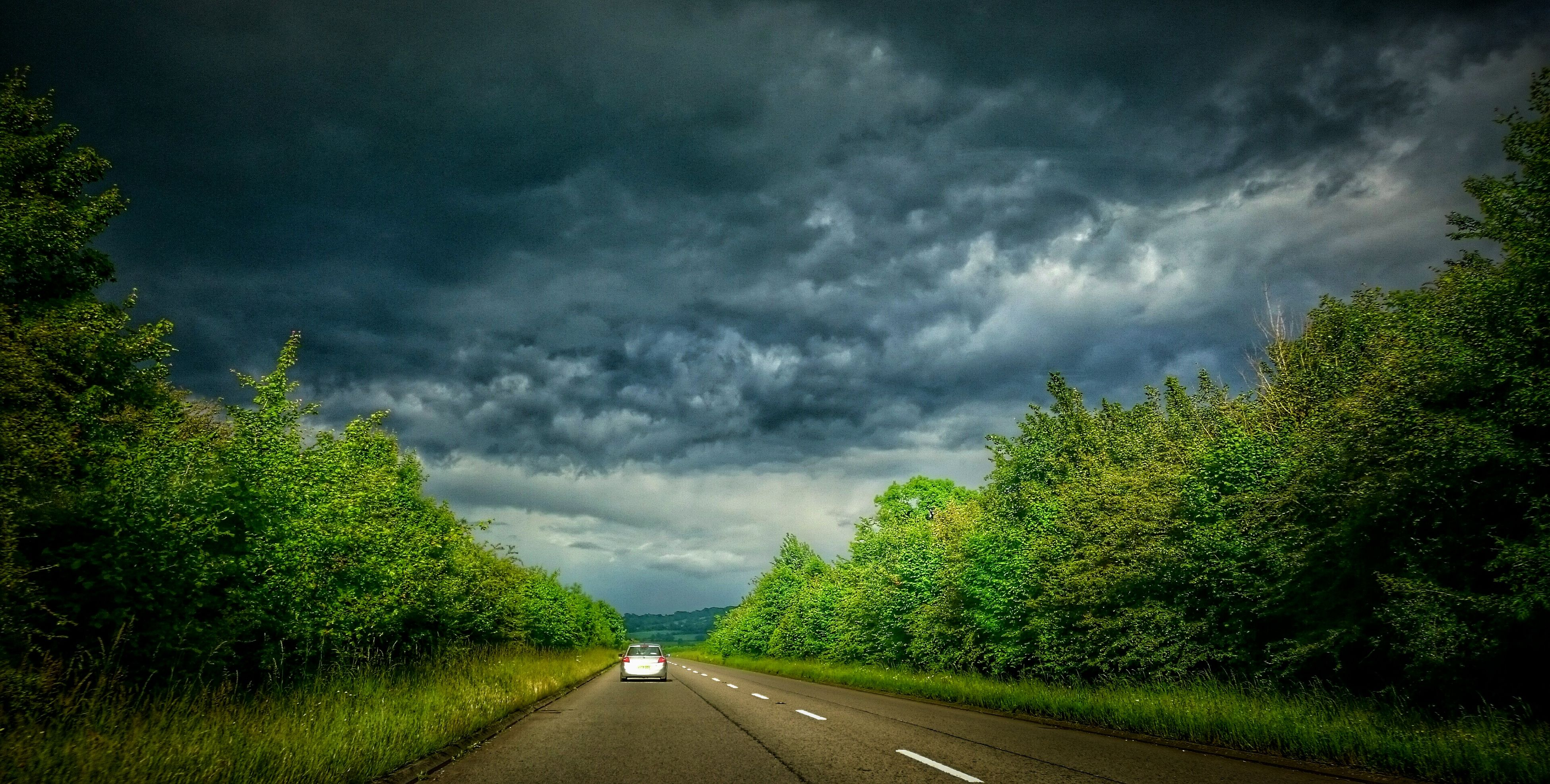 the way forward, transportation, road, sky, cloud - sky, diminishing perspective, cloudy, tree, vanishing point, road marking, country road, car, weather, cloud, storm cloud, land vehicle, nature, street, overcast, mode of transport