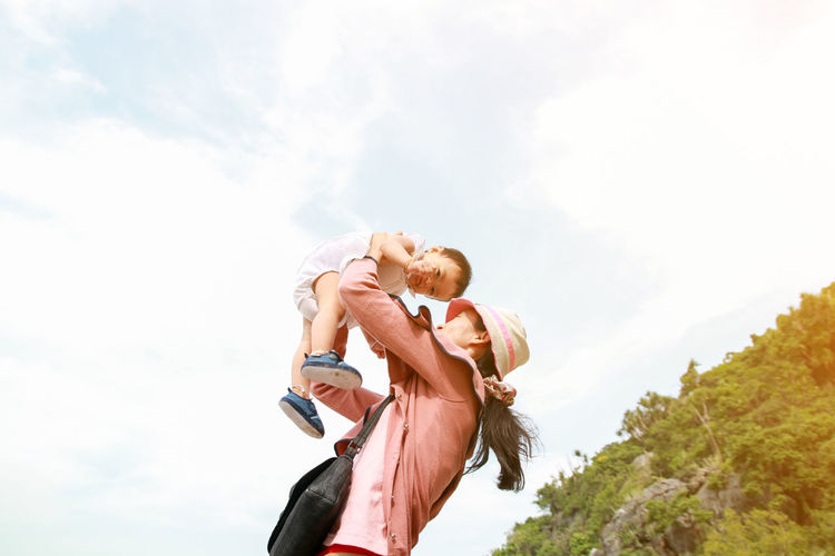 Happy family concept, Young mother jolly with her baby Bonding Carrying Cheerful Childhood Cloud - Sky Daughter Day Enjoyment Family With One Child Fun Girls Happiness Leisure Activity Lifestyles Love Low Angle View Men Nature Outdoors Piggyback Real People Sky Smiling Togetherness Women