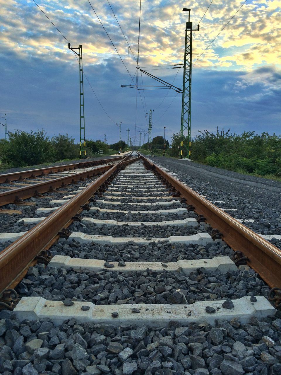 railroad track, rail transportation, transportation, cable, gravel, railroad tie, sky, diminishing perspective, cloud - sky, electricity, metal, electricity pylon, no people, rock - object, parallel, power supply, connection, power line, day, the way forward, railway track, nature, outdoors
