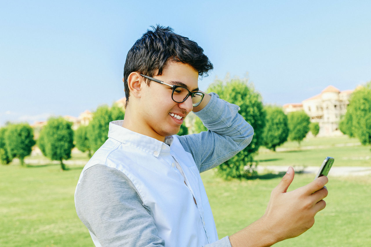 Casual Clothing Communication Connection Eyeglasses  Glasses Holding Leisure Activity Lifestyles Mobile Mobile Phone Nature One Person Outdoors Phone Portable Information Device Real People Side View Smart Phone Smile Technology Tree Using Phone Wireless Technology Young Adult Young Men
