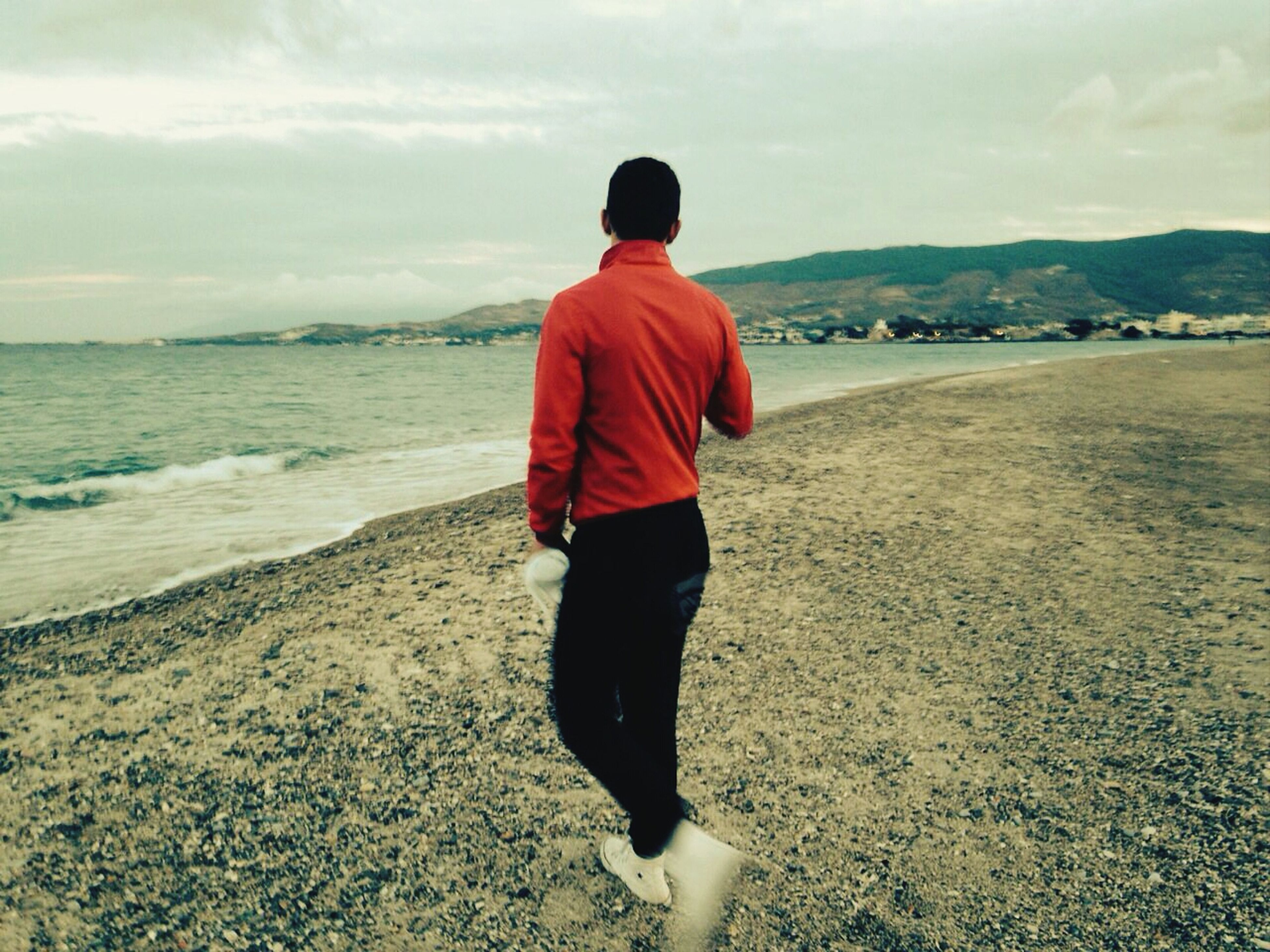 sky, beach, rear view, sea, tranquil scene, water, full length, tranquility, standing, scenics, beauty in nature, lifestyles, shore, leisure activity, cloud - sky, nature, casual clothing, sand