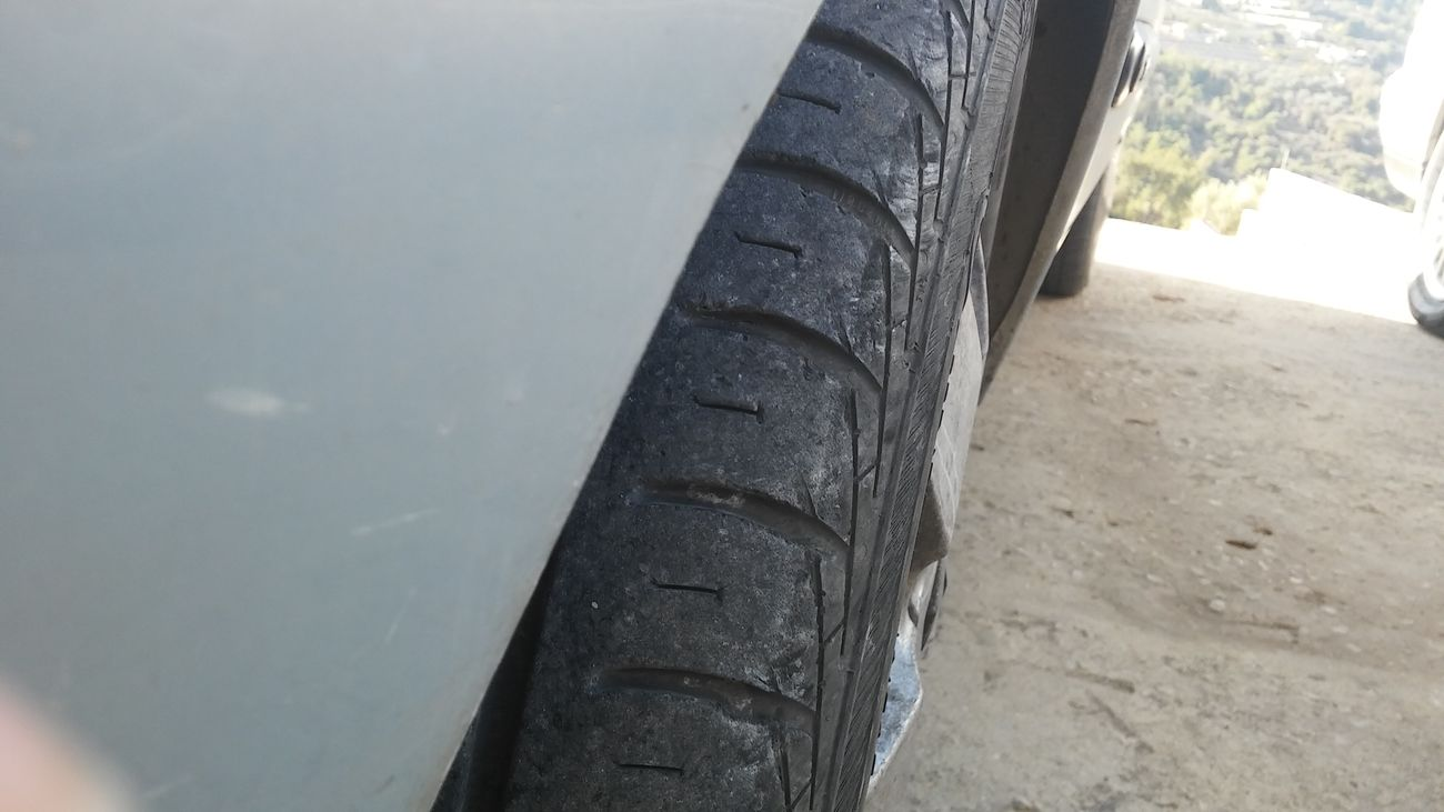 Car Wheel Grip Asphalt Close-up Outdoors Day Mountain Grass Tree Trees And Sky