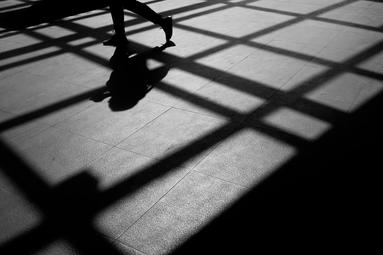 Shadow Of Person Walking On Tiled Floor