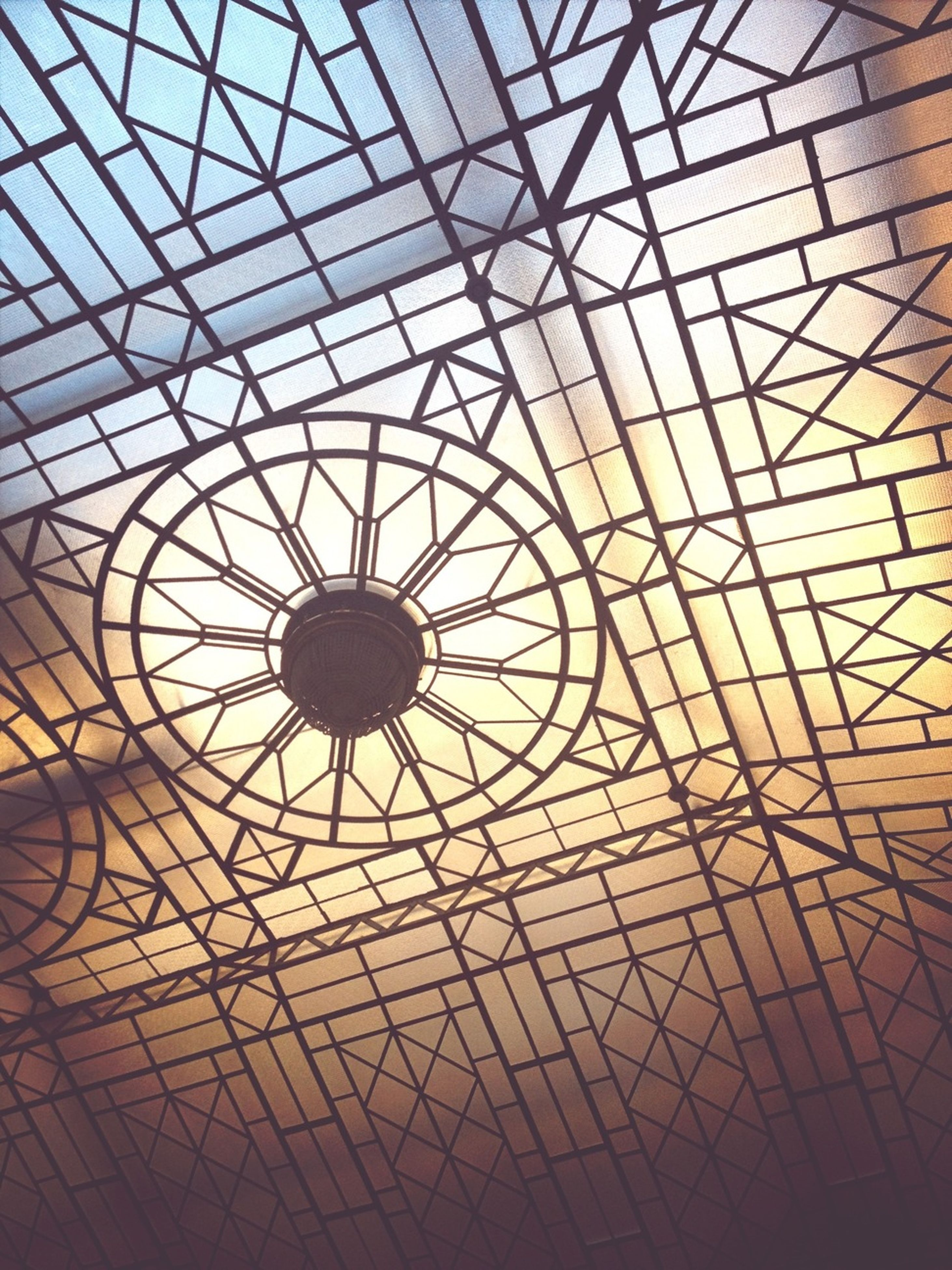 indoors, ceiling, pattern, architecture, built structure, design, full frame, geometric shape, backgrounds, skylight, architectural feature, low angle view, glass - material, circle, directly below, no people, modern, metal, shape, grid