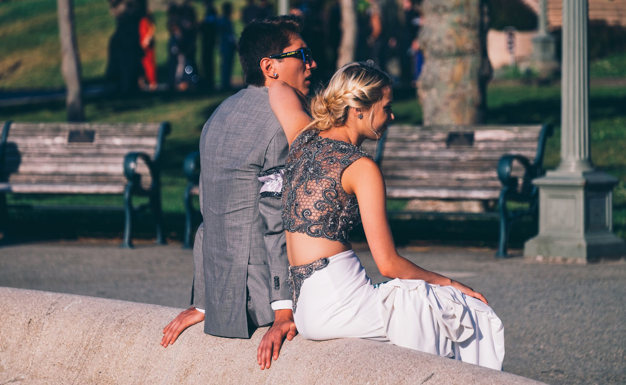 two people, togetherness, real people, focus on foreground, casual clothing, outdoors, young women, love, day, young adult, leisure activity, sitting, full length, relaxation, park - man made space, sunlight, lifestyles, women, smiling, blond hair, retaining wall, nature, grass, friendship