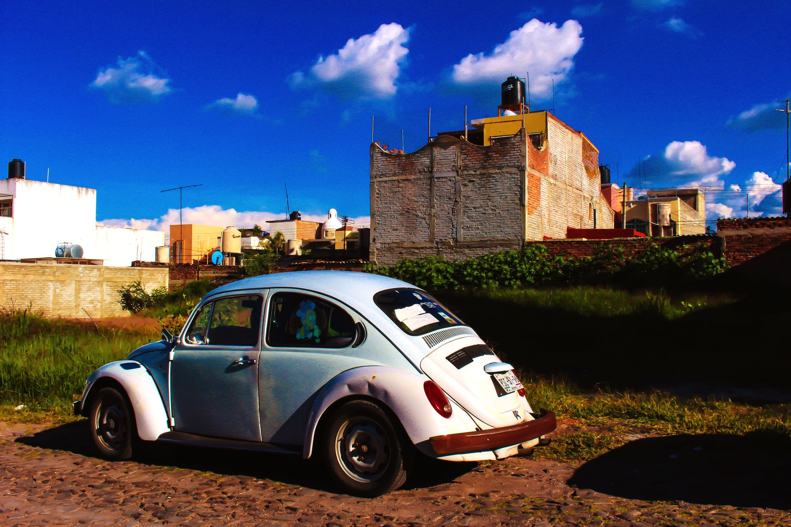 building exterior, architecture, built structure, transportation, sky, land vehicle, car, mode of transport, blue, road, cloud, day, cloud - sky, grass, sunlight, old, street, outdoors, abandoned, no people