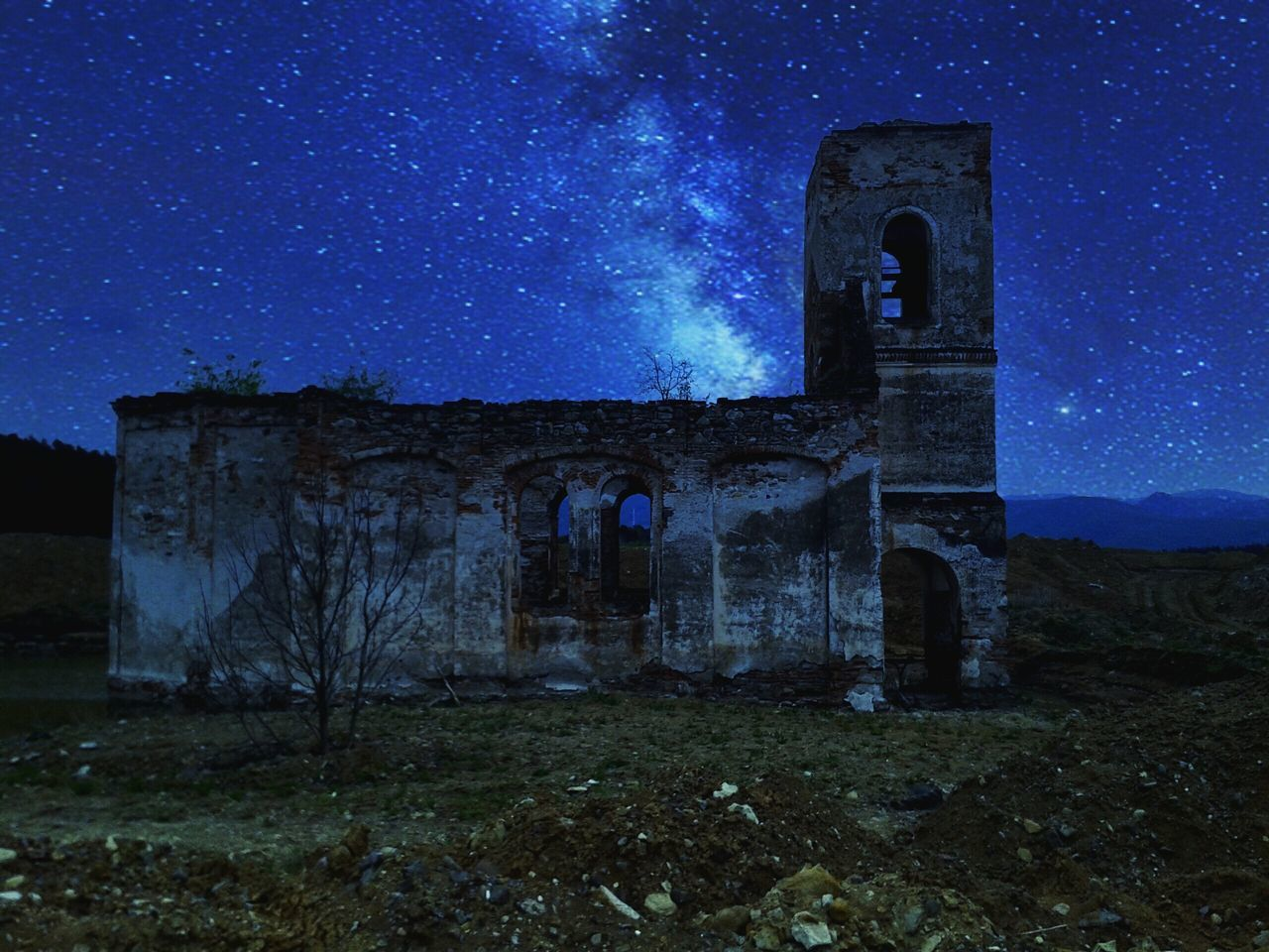 Low Angle View Of Old Church Against Star Blue Field At Night