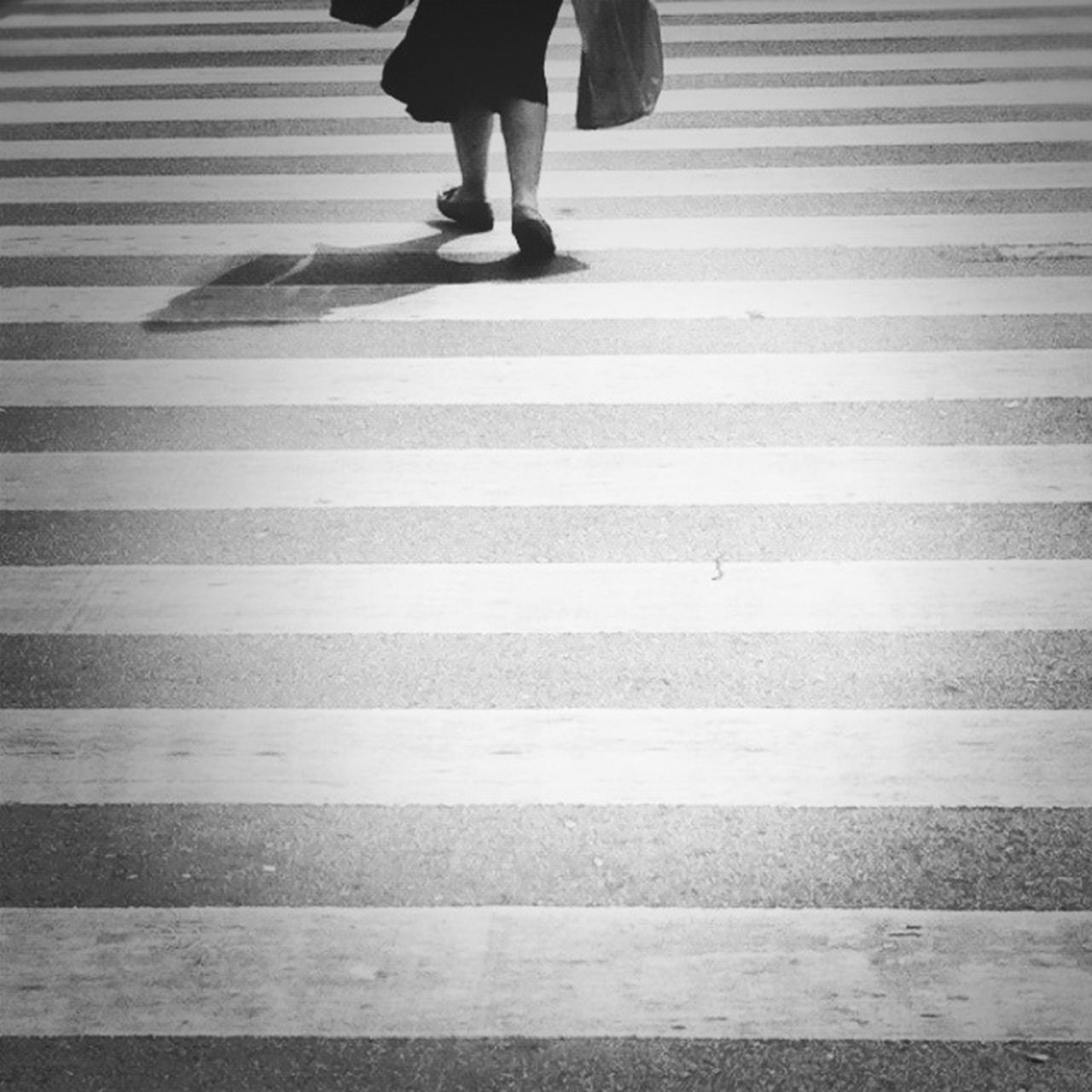 zebra crossing, low section, human leg, walking, striped, road marking, crossing, human foot, transportation, one person, street, real people, pedestrian, rear view, road, white line, women, city life, lifestyles, human body part, standing, day, city, outdoors, adult, people, adults only