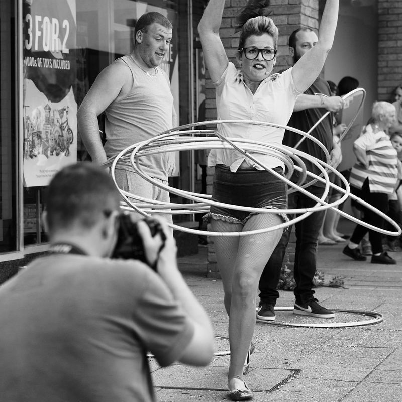 A street entertainer Action Crowd Girl Hoola Hoop Hoops Photographer Shop Show Spectators Store Street Entertainer