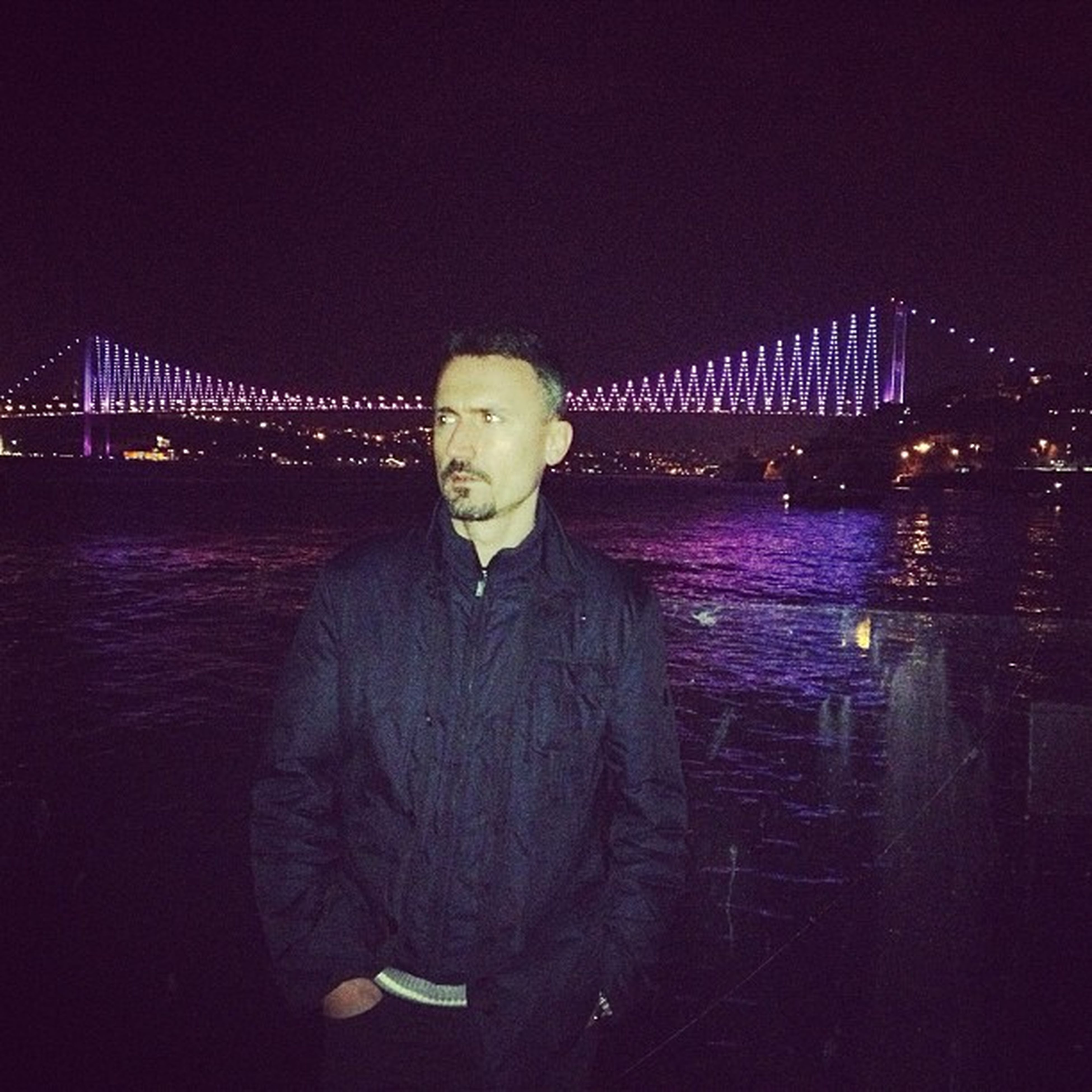 night, water, illuminated, rear view, standing, lifestyles, leisure activity, built structure, casual clothing, architecture, river, full length, waist up, three quarter length, bridge - man made structure, connection, reflection, clear sky