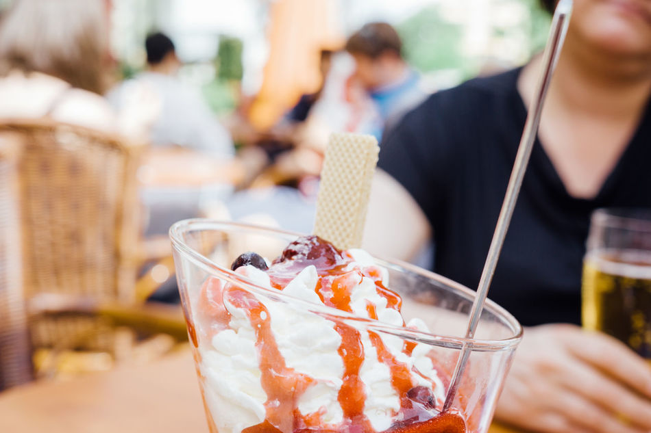 Glass of ice cream with whipped cream and berry sauce on table, outdoors Berlin Berries Berry Sauce Close-up Eating Focus On Foreground Food Freshness Germany Ice Cream Indulgence Liquid Ready-to-eat Red Refreshment Whipped Cream Yummy