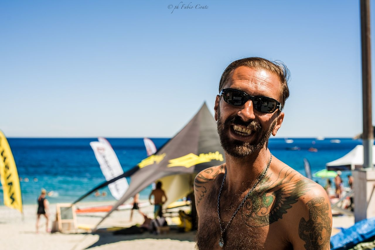 sea, real people, sunglasses, one person, focus on foreground, lifestyles, incidental people, beard, leisure activity, sky, water, looking at camera, day, outdoors, front view, nature, horizon over water, sunlight, clear sky, portrait, shirtless, smiling, eyeglasses, beauty in nature, young adult, close-up