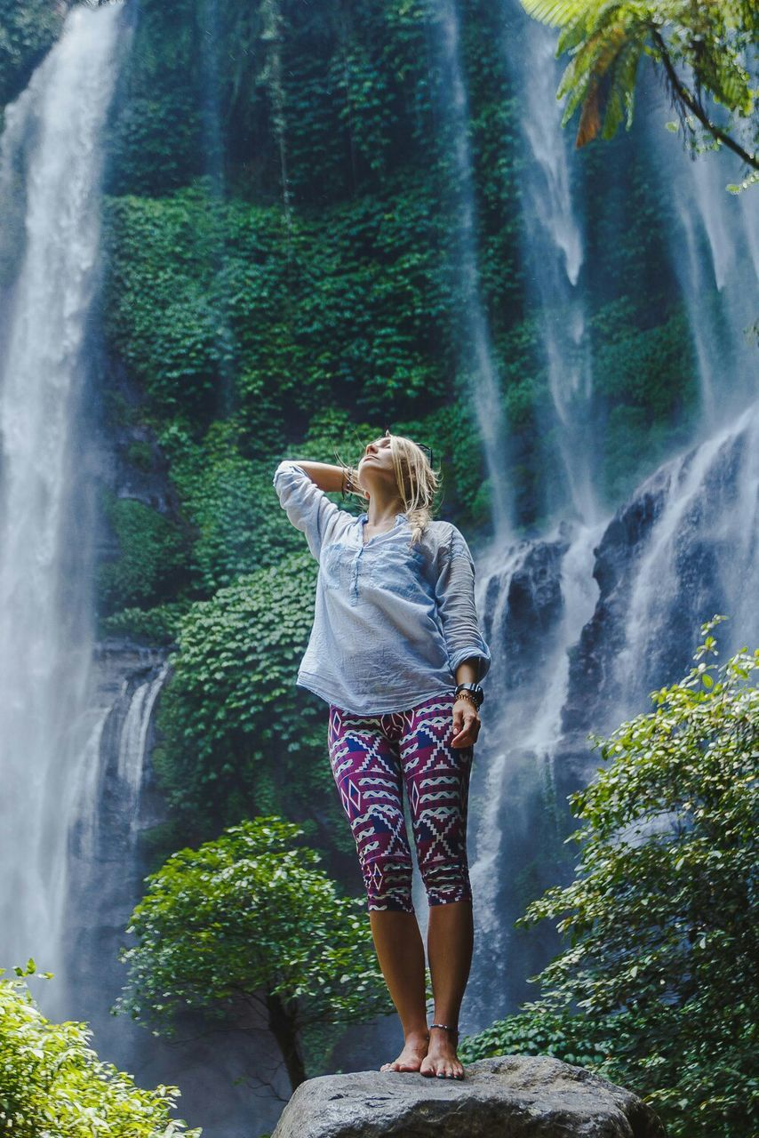 Full Length Of Woman Standing On Rock Against Waterfall At Forest