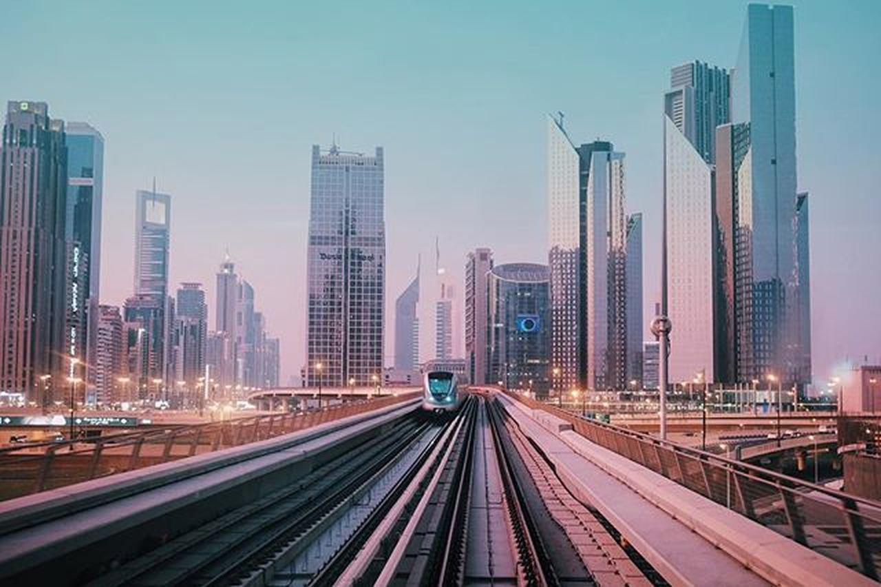 skyscraper, urban skyline, city, architecture, transportation, illuminated, building exterior, downtown district, speed, sky, city life, night, modern, business finance and industry, cityscape, railroad track, built structure, long exposure, the way forward, outdoors, no people, clear sky, travel destinations, business, futuristic