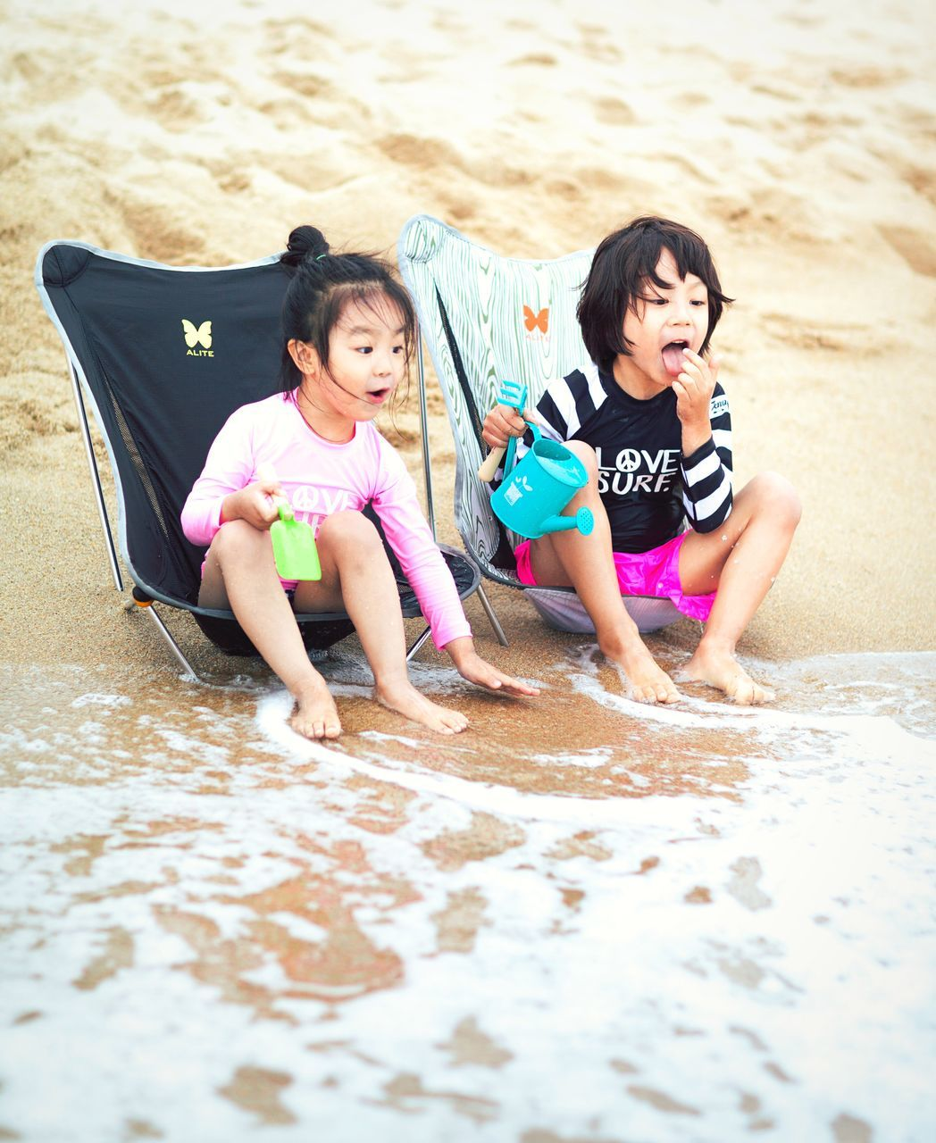 sand, beach, childhood, girls, real people, elementary age, vacations, full length, outdoors, sibling, leisure activity, togetherness, day, child, playing, sitting, summer, two people, happiness, water, sand pail and shovel, friendship, human hand, people
