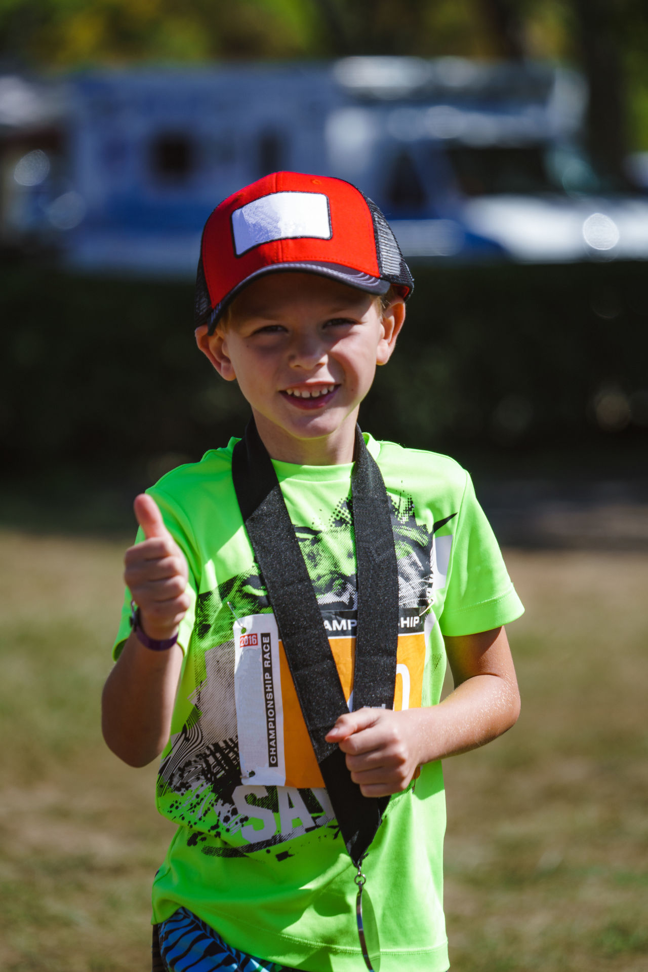 Young boy winning the race wearing his new medal on a beautiful sunny day Child Childhood Children Only Competing Competitor Day Front View Happy Lifestyle Lifestyles Medal One Person Outdoors Outdoors Photograpghy  People Smiling Sport Success Sunny TRIATHLON Trophy Winning