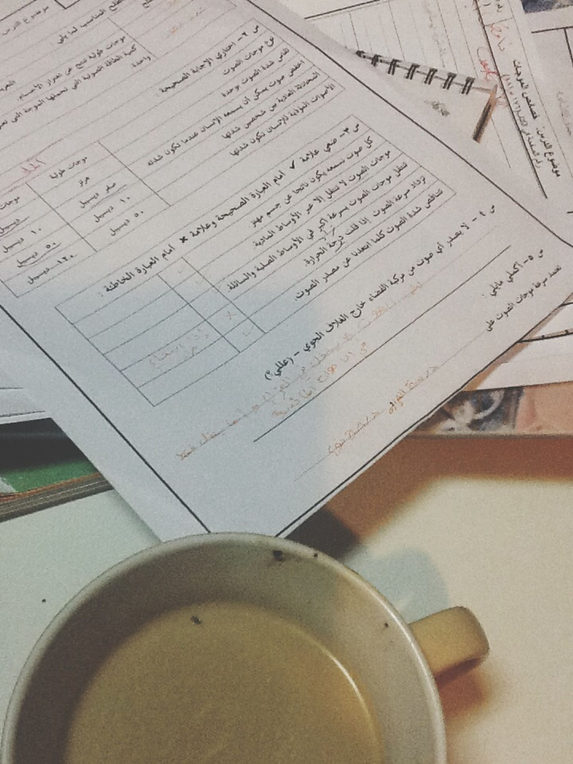 indoors, communication, text, book, table, close-up, still life, western script, paper, education, high angle view, pen, no people, technology, open, number, page, selective focus, coffee cup, part of