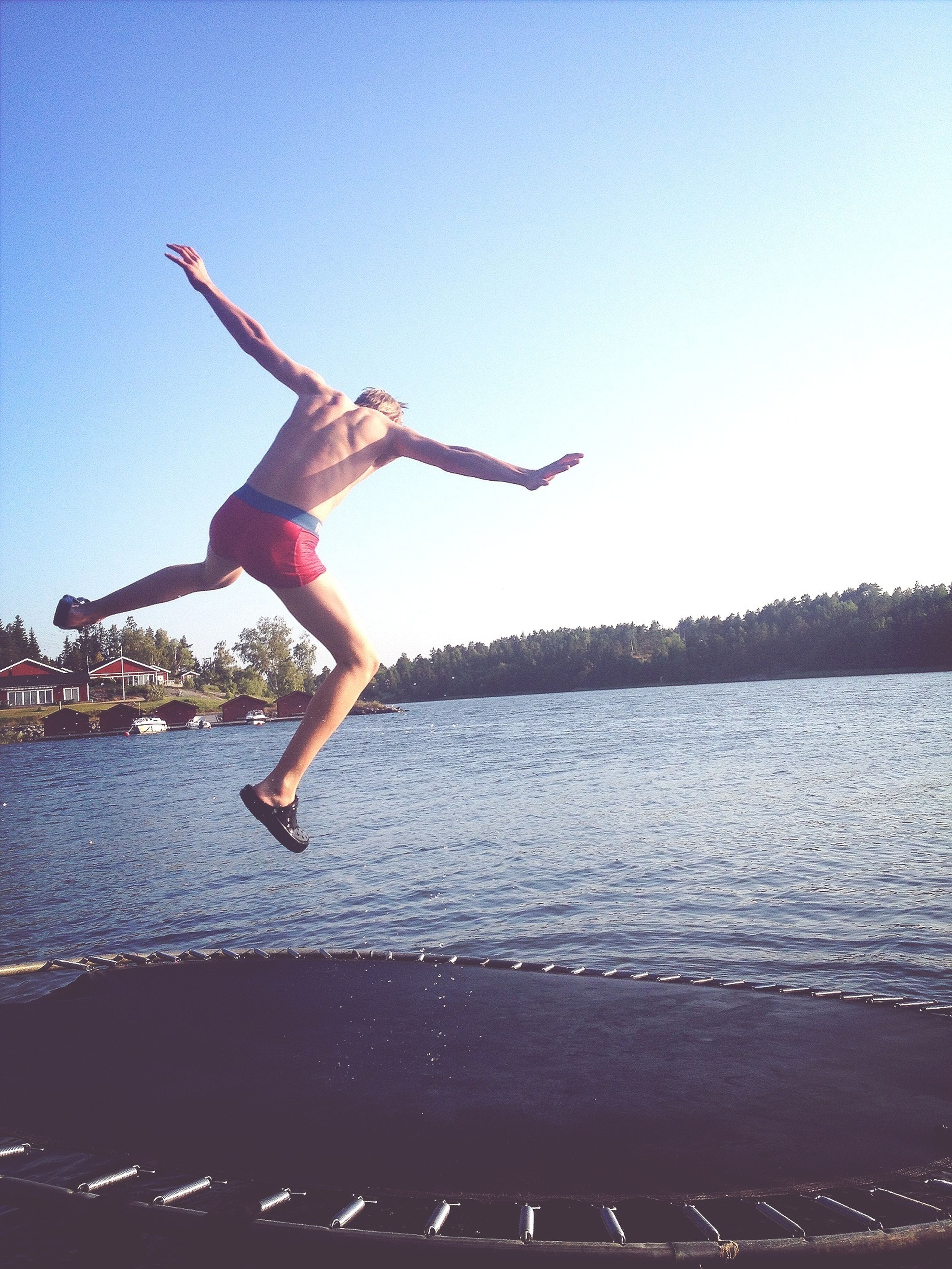 water, mid-air, clear sky, lifestyles, leisure activity, full length, flying, arms outstretched, sky, jumping, motion, sea, freedom, young adult, skill, copy space, blue, holding