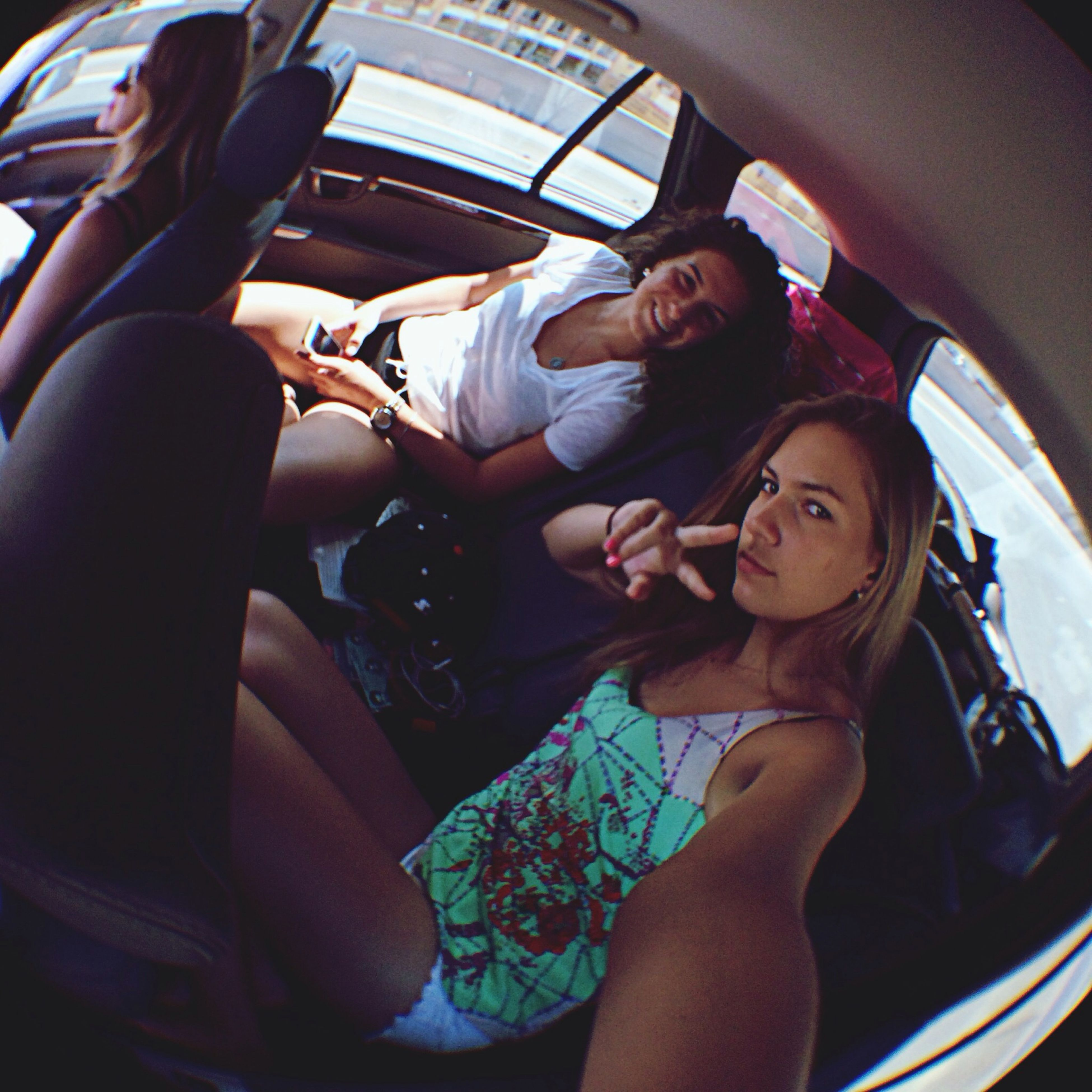 lifestyles, young adult, person, sitting, leisure activity, young women, indoors, casual clothing, togetherness, vehicle interior, transportation, relaxation, front view, holding, smiling, bonding