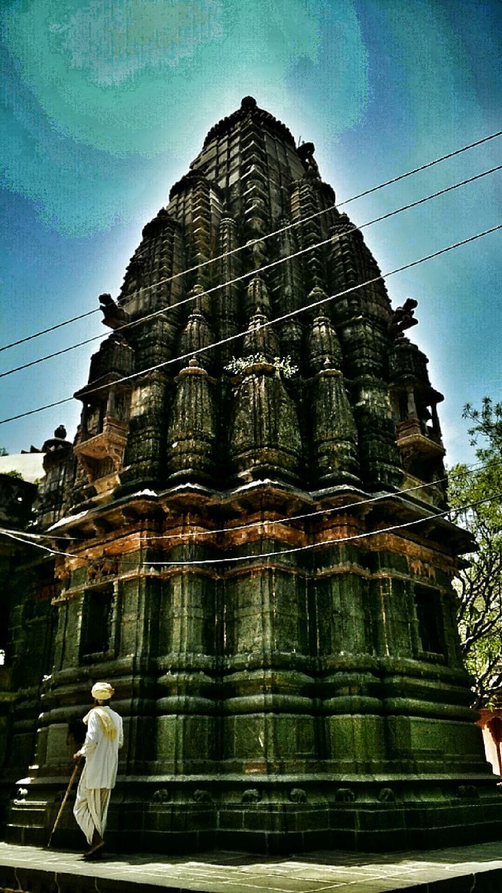 spirituality, religion, architecture, place of worship, low angle view, building exterior, built structure, statue, sky, day, outdoors, tree, no people