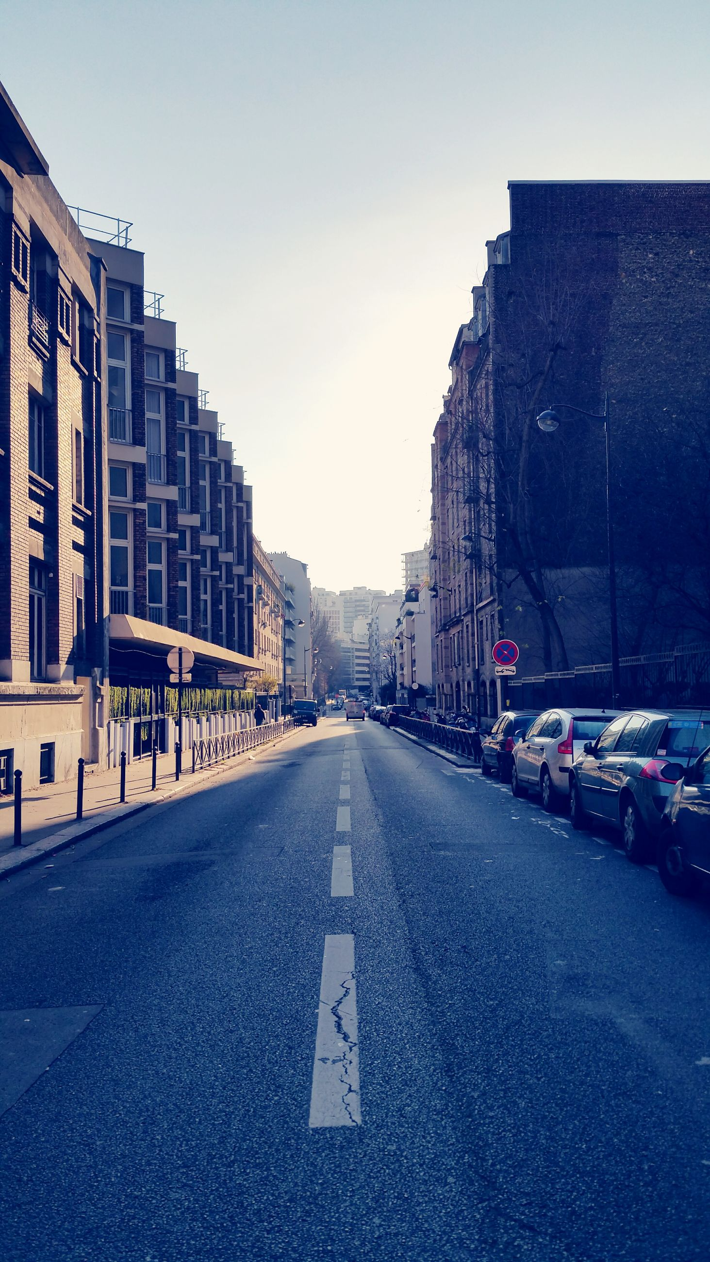 building exterior, architecture, the way forward, built structure, transportation, street, city, road, diminishing perspective, road marking, car, vanishing point, clear sky, land vehicle, city street, building, mode of transport, city life, asphalt, empty