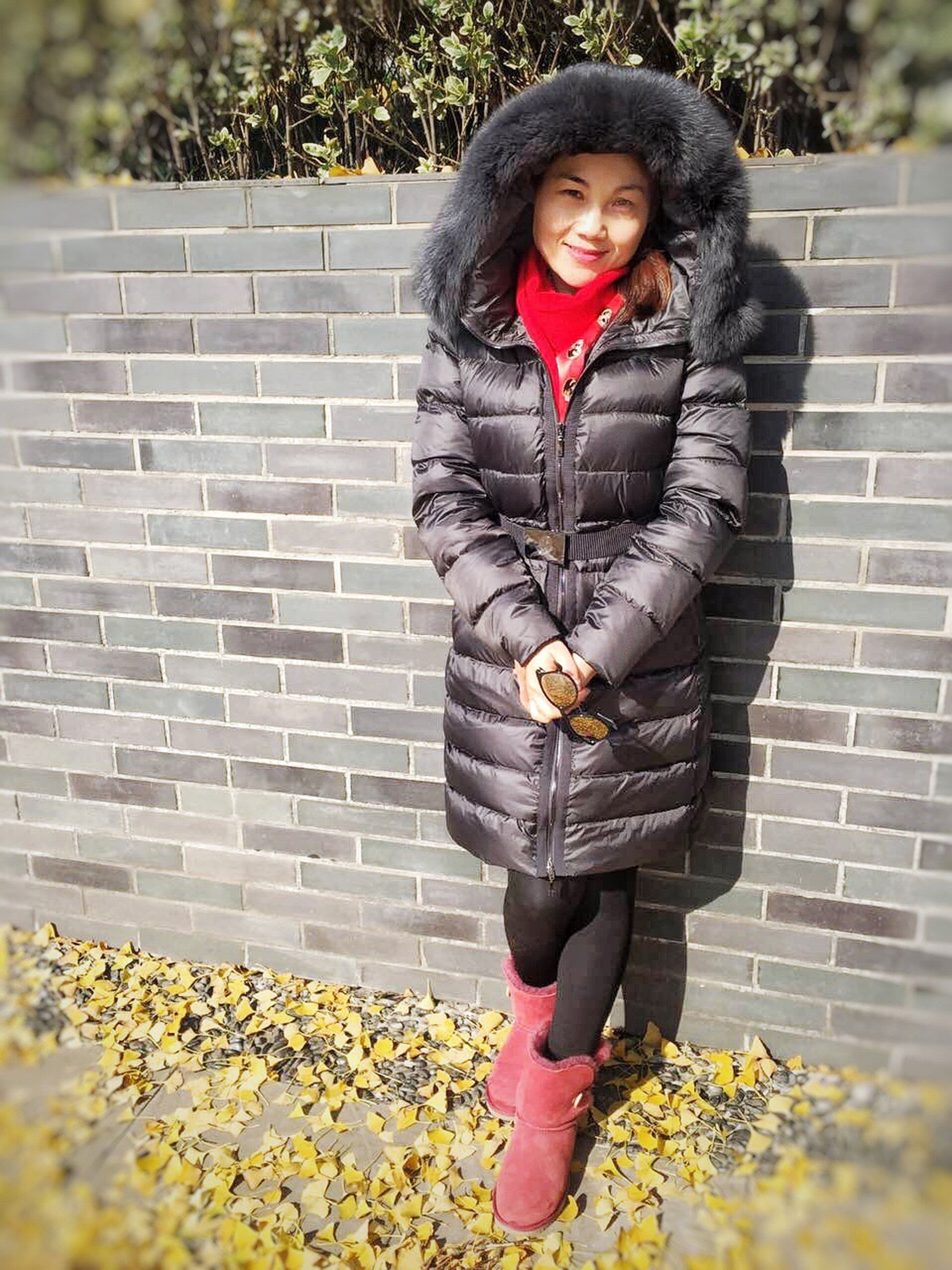 person, casual clothing, lifestyles, front view, young adult, standing, full length, looking at camera, portrait, leisure activity, young women, smiling, holding, building exterior, three quarter length, brick wall
