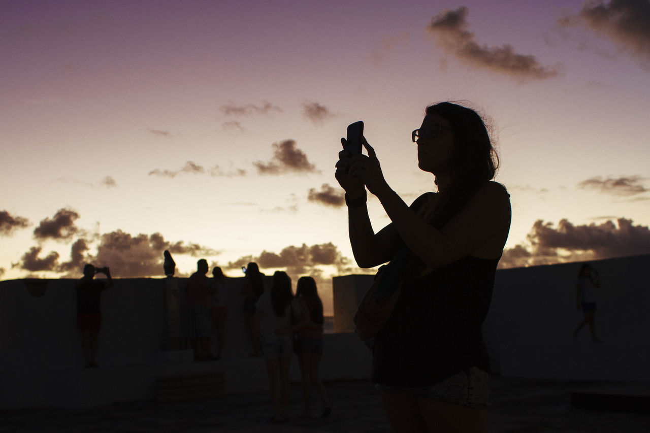 Young woman uses the mobile to capture a stuning sunset Adult Holding Leisure Activity Lifestyles One Person Photographing Real People Silhouette Sky Sommer Sunset Women