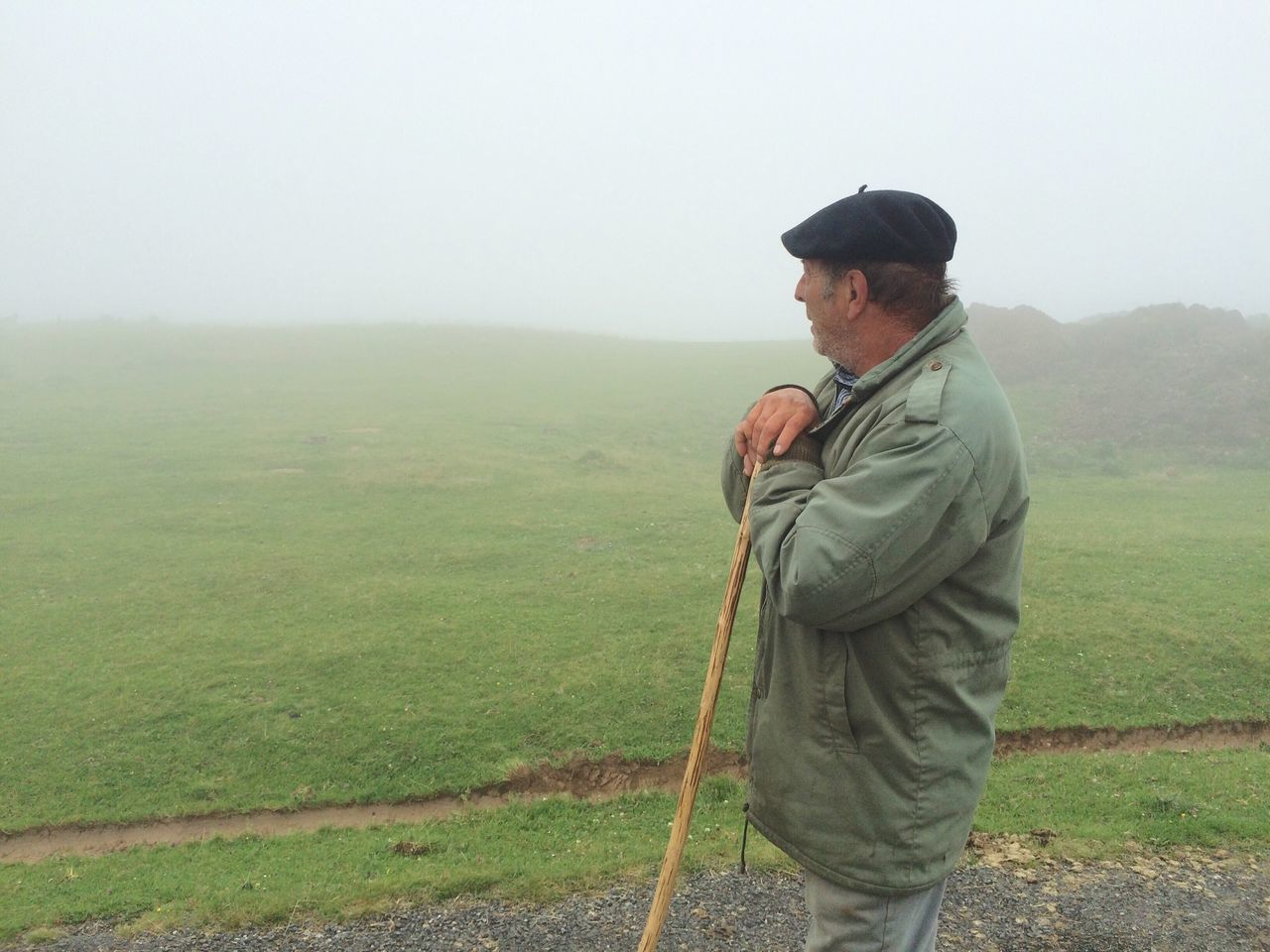 Senior Man Holding Cane While Standing On Road By Field Against Sky In Foggy Weather