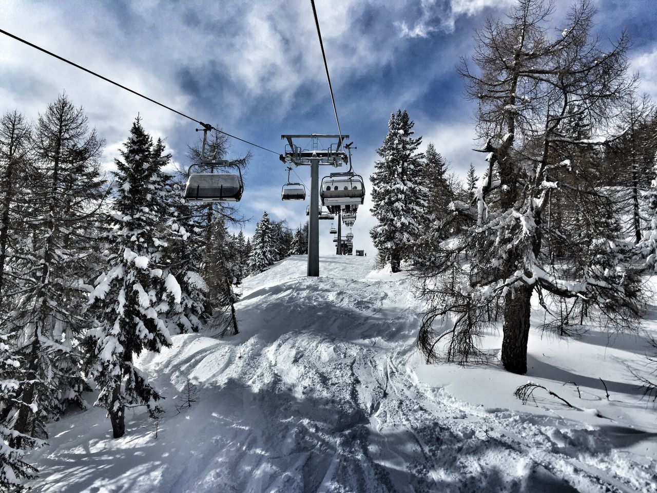 Low Angle View Of Ski Lift Over Snowy Field Against Sky