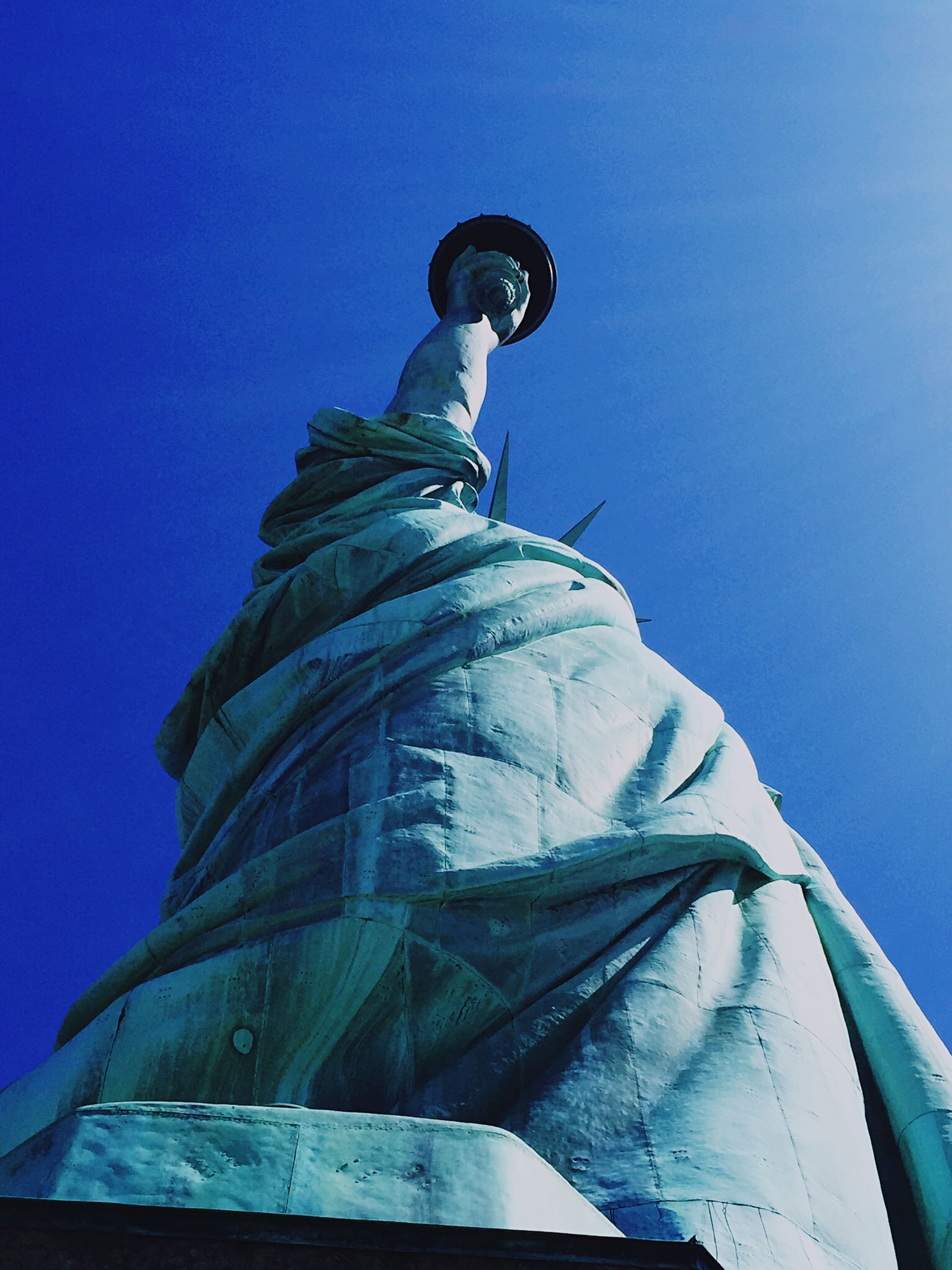 low angle view, blue, human representation, statue, sculpture, clear sky, art and craft, art, creativity, built structure, copy space, religion, famous place, day, architecture, outdoors, sky, spirituality