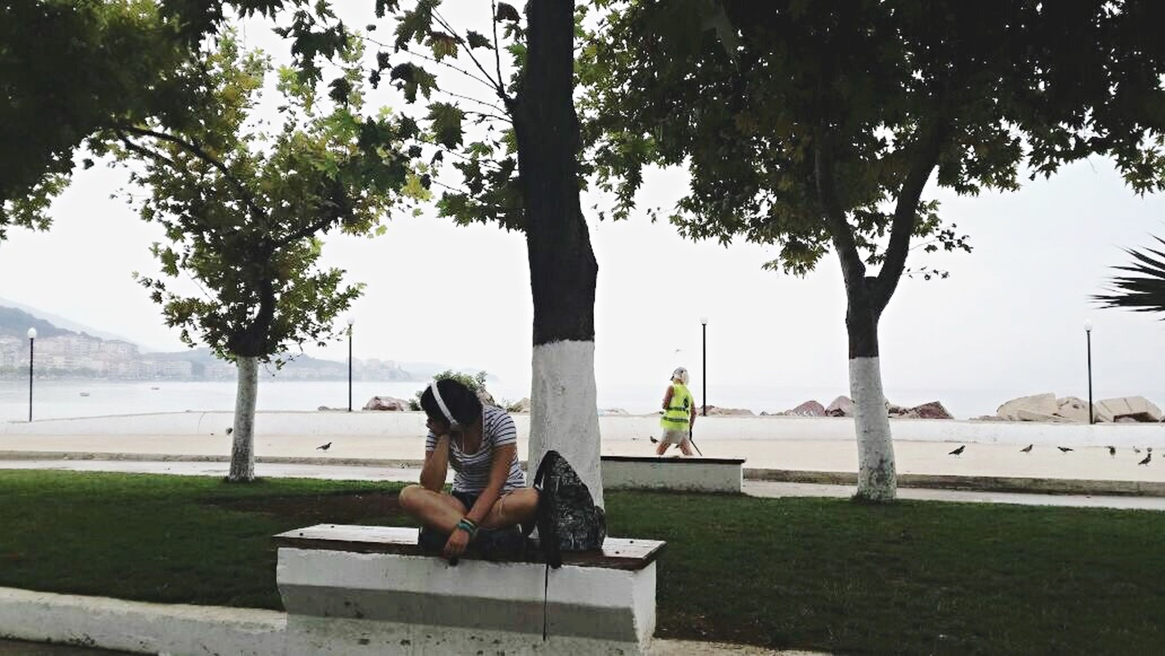 sitting, leisure activity, lifestyles, relaxation, tree, rear view, person, full length, bench, water, young adult, casual clothing, young women, grass, day, park - man made space, vacations, resting