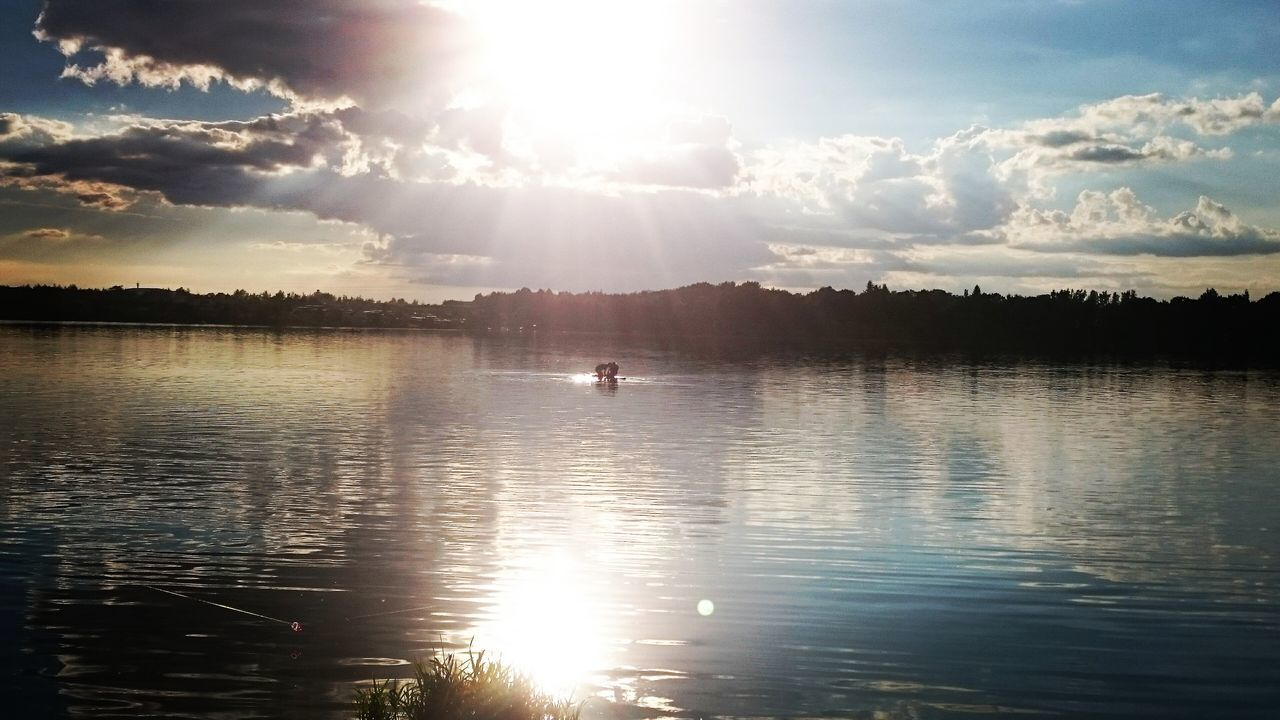 water, lens flare, sunbeam, nature, sky, sunlight, beauty in nature, tranquility, scenics, sun, sunset, reflection, tranquil scene, outdoors, cloud - sky, silhouette, waterfront, lake, tree, real people, day, travel destinations, paddleboarding
