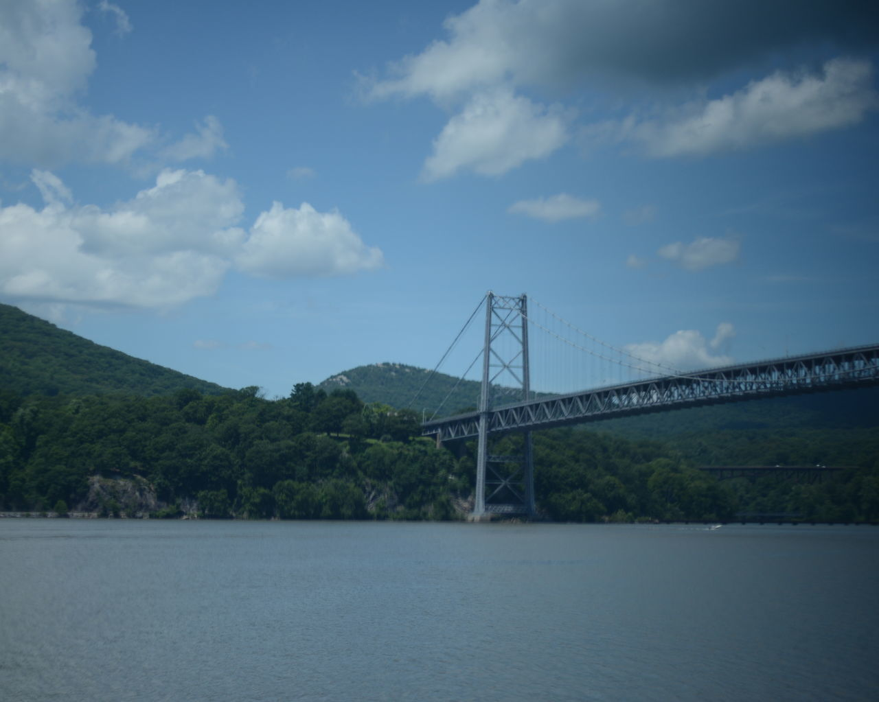 bridge - man made structure, connection, architecture, engineering, suspension bridge, river, built structure, no people, transportation, sky, outdoors, nature, water, bridge, travel, waterfront, day, travel destinations, cloud - sky, beauty in nature, chain bridge