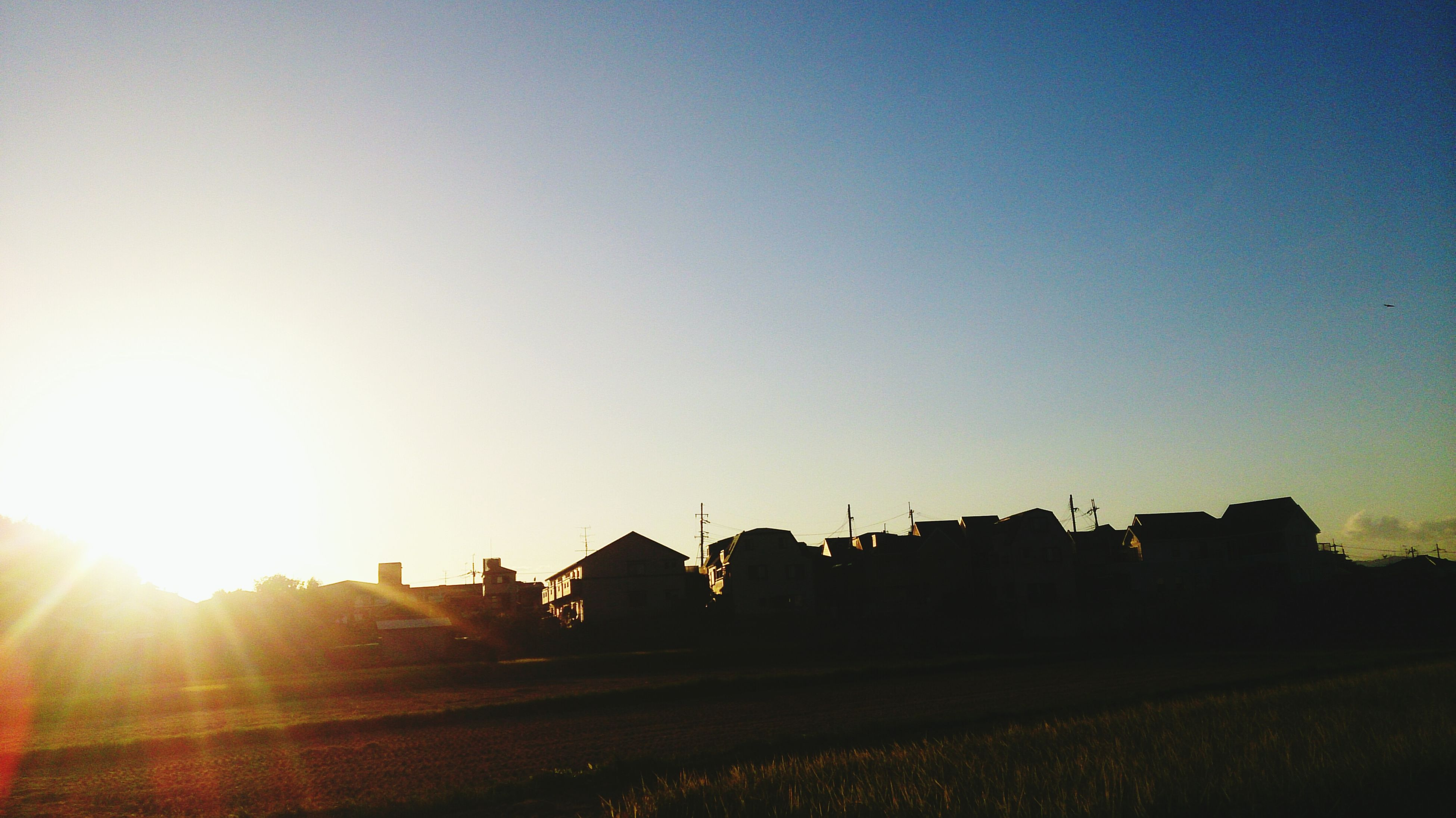 building exterior, architecture, built structure, sun, clear sky, sunset, sunlight, copy space, sunbeam, silhouette, lens flare, house, residential structure, sky, outdoors, residential building, building, nature, bright, city