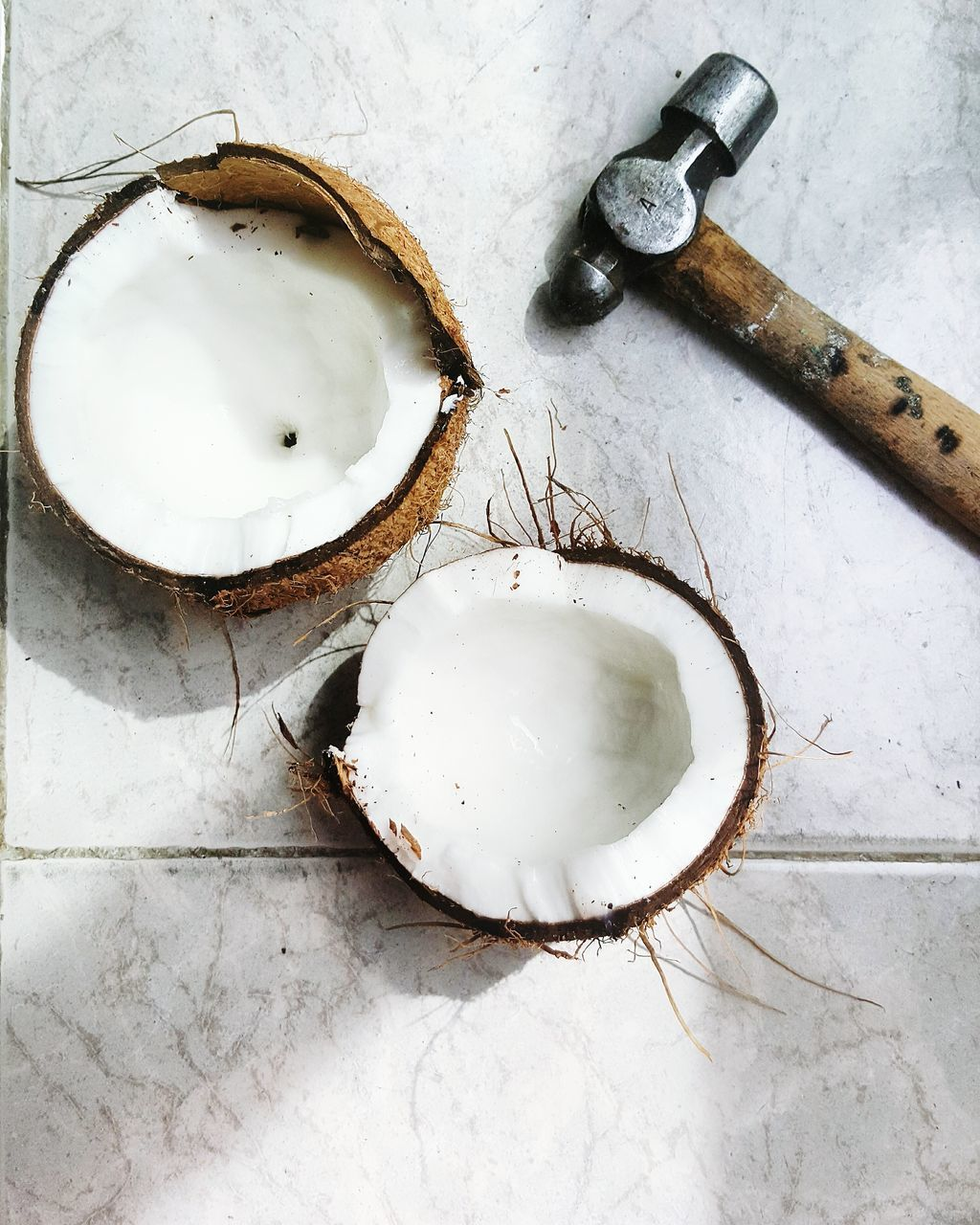 Directly Above View Of Coconut And Hammer On Tiled Floor At Home