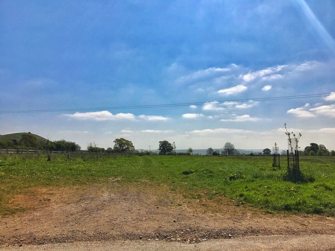 field, landscape, sky, cloud - sky, no people, agriculture, day, nature, outdoors, grass, beauty in nature, road, tree, scenics, electricity pylon