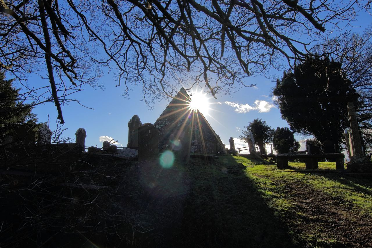 Pyramid tomb on a sunny day. Architecture Architecture Branch Cemetery Cultures Death Grass Grave Ireland Lens Flare Mausoleum No People Outdoors Pyramid Shadow Sky Structure Sun Sunbeam Sunlight Tombstone Tourism Tree Water