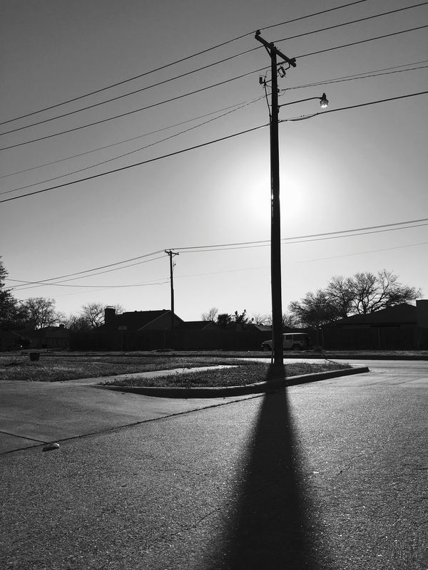 Black and white photo of sun behind power pole creating a silhouette and long shadow. Black & White Black And White Blackandwhite Blackandwhite Photography Contrast IPhoneography Iphonephotography Monochromatic Monochrome Nature Power Line  Shades Of Grey Shadow Shadows Shadows & Lights Silhouette Sky Streetphoto_bw Streetphotography Sun Sunset