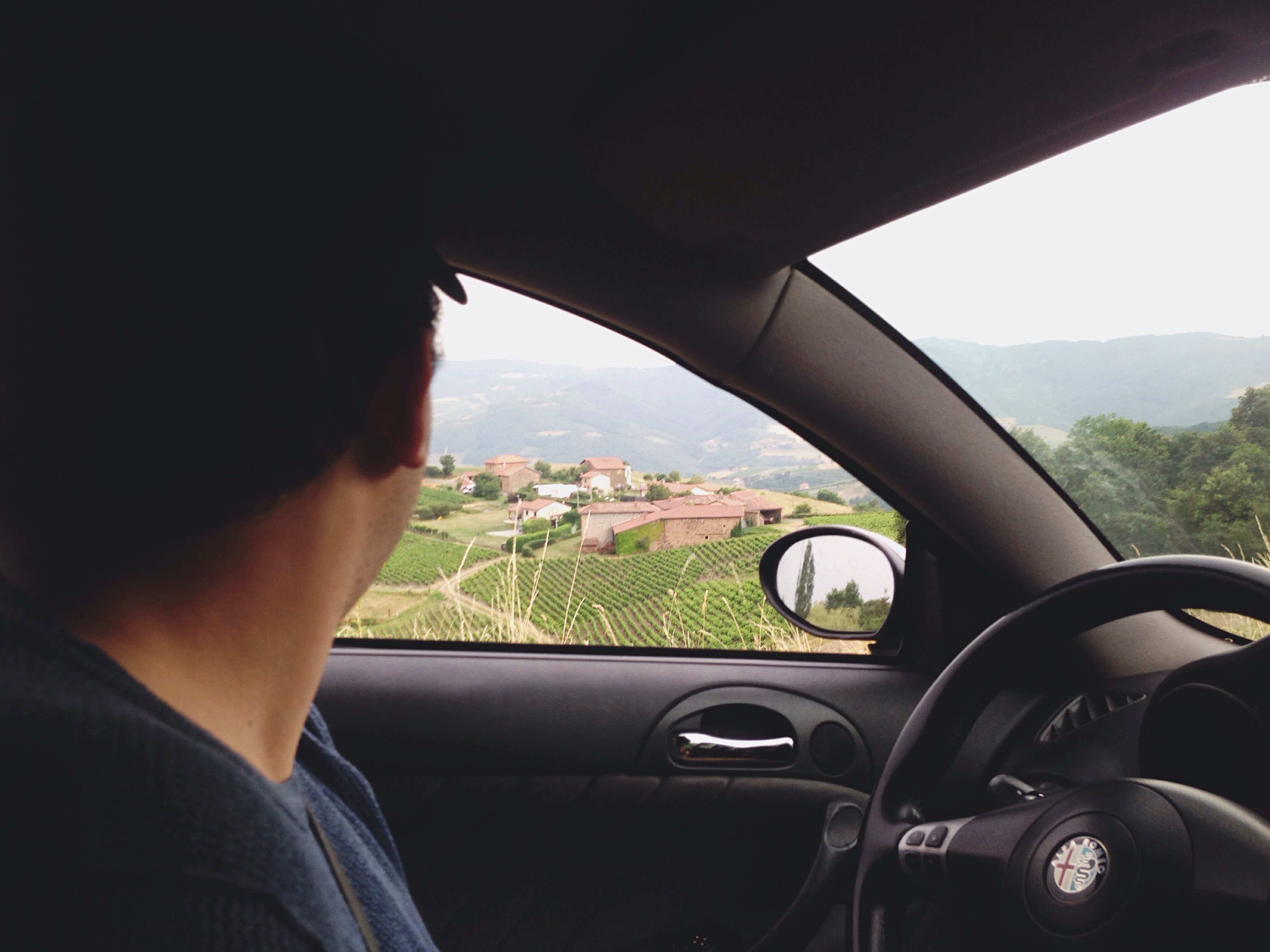 transportation, mode of transport, land vehicle, vehicle interior, car interior, part of, side-view mirror, sky, cropped, driving, landscape, journey, lifestyles, rear-view mirror, windshield, personal perspective, leisure activity, steering wheel, mountain, nature, close-up, day