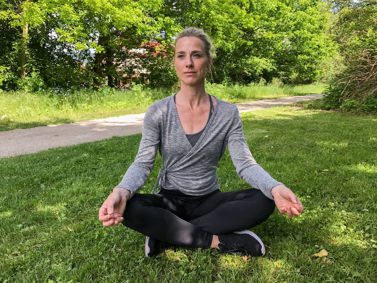 Beautiful Woman Blond Hair Confidence  Cross-legged Day Front View Full Length Grass Growth Happiness Leisure Activity Lifestyles Looking At Camera Nature One Person Outdoors Park - Man Made Space Portrait Real People Relaxation Sitting Tree Yoga Young Adult Young Women