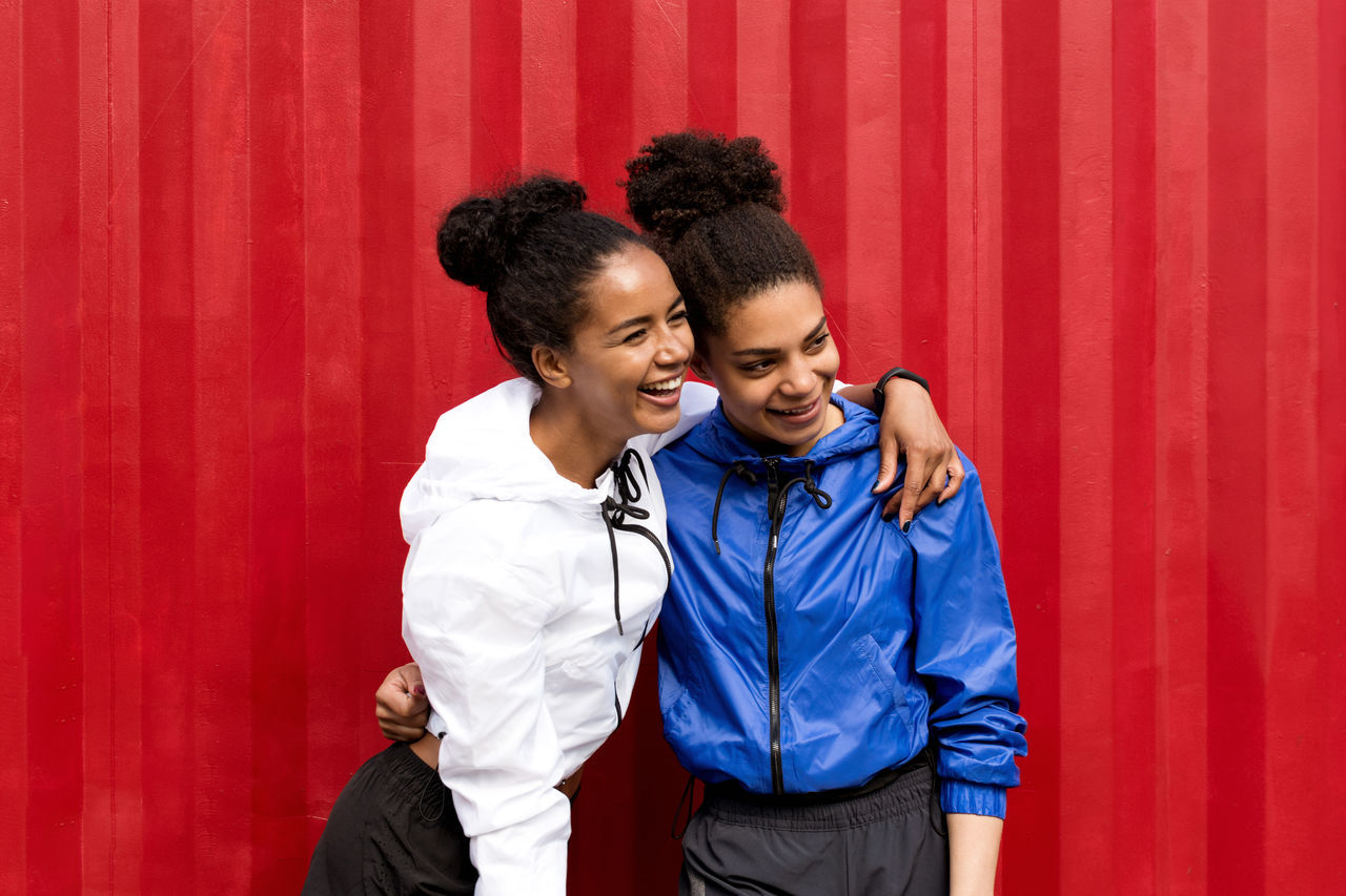 Arm Around Cheerful Day Female Fitness Friendship Front View Happiness Healthy Lifestyle Lifestyles Outdoors Portrait Real People Red Smiling Sport Sport Clothes Standing Togetherness Two People Well-dressed Young Adult Young Women